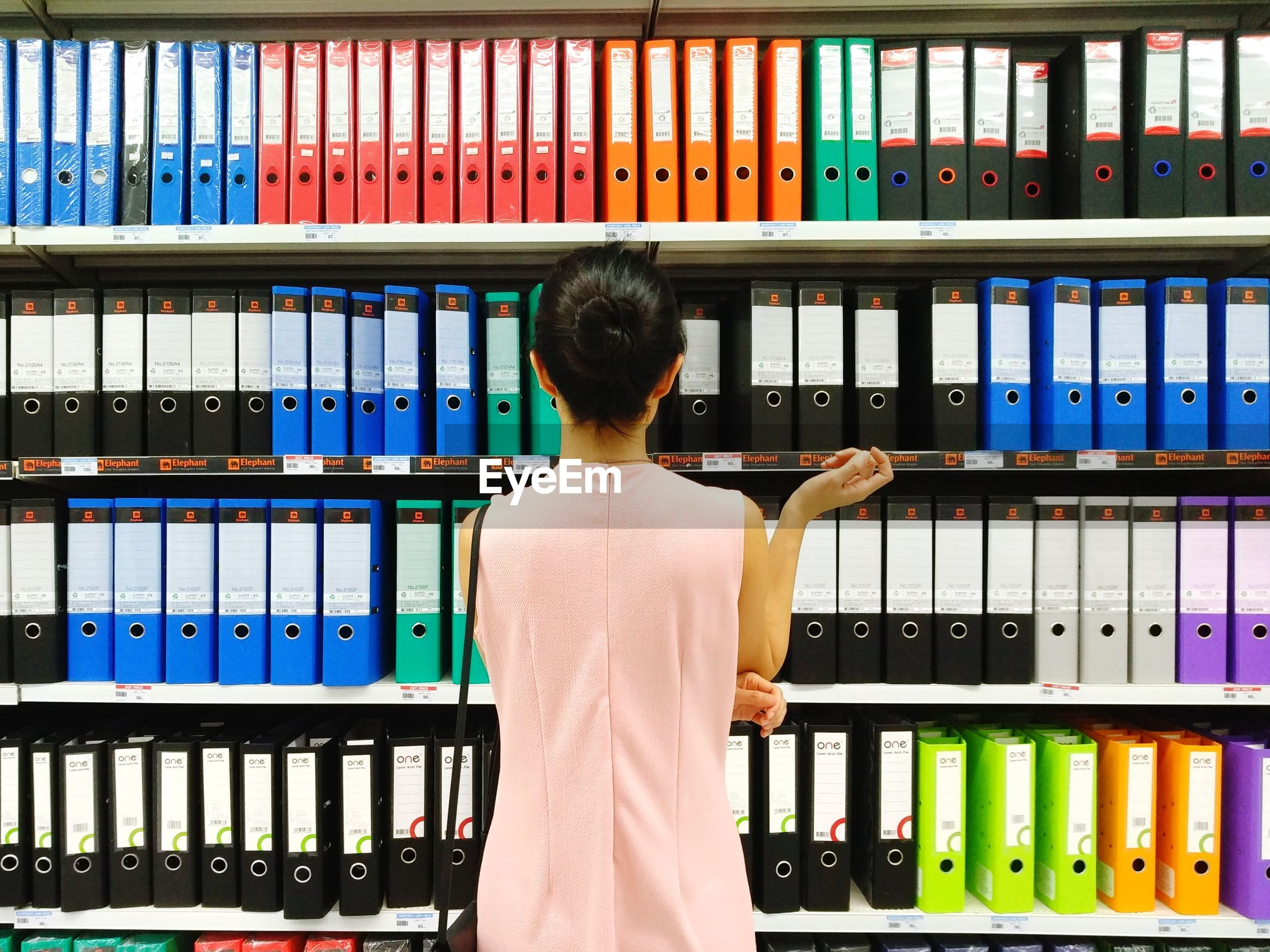 Rear view of woman standing against shelf at office