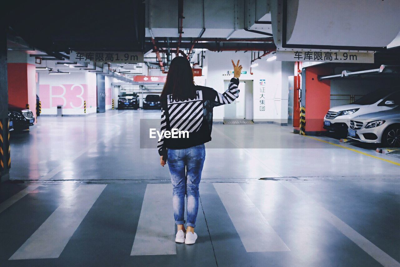 Rear View Full Length Of Woman Showing Peace Sign In Underground Parking Lot