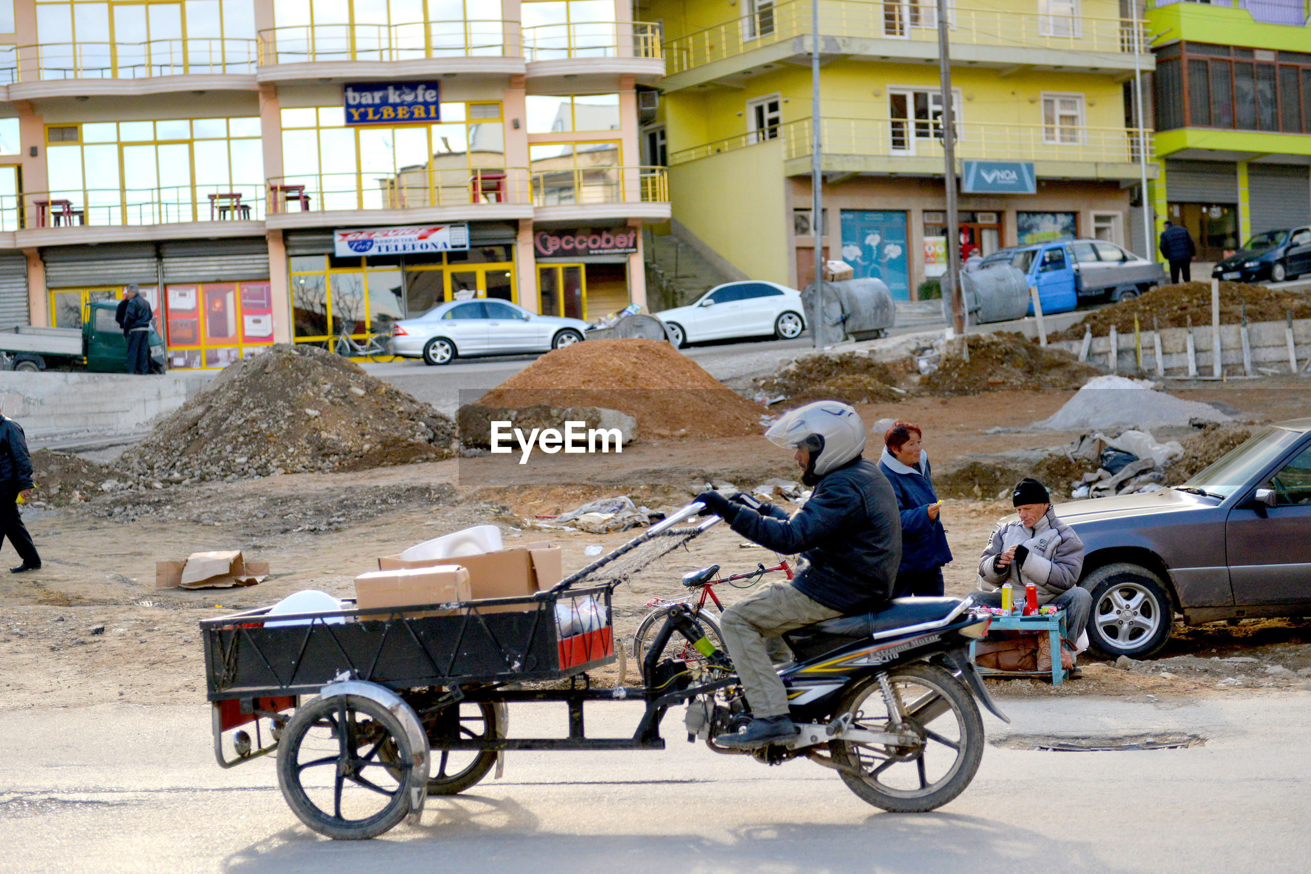 transportation, mode of transport, full length, architecture, street, day, outdoors, land vehicle, city life, road, built structure, one person, real people, city, men, building exterior, occupation, one man only, working, only men, adult, adults only, young adult, people