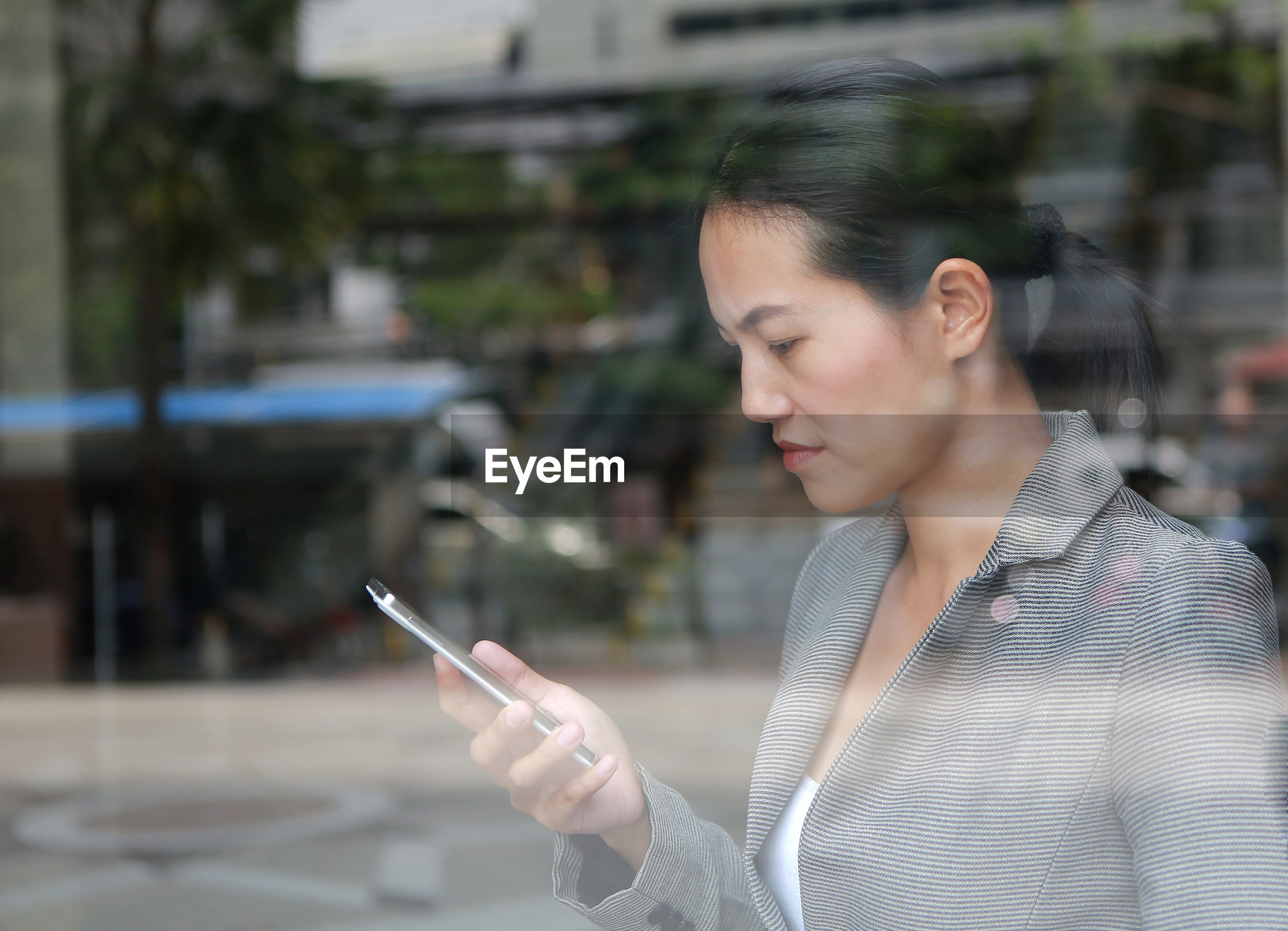 Serious businesswoman using smart phone seen through window