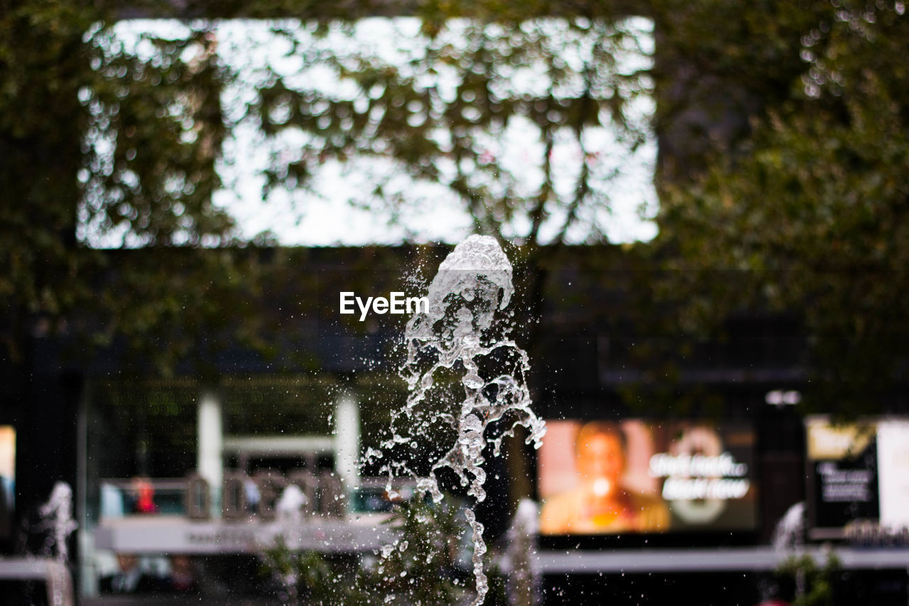water, architecture, focus on foreground, nature, motion, no people, plant, day, building exterior, spraying, outdoors, built structure, selective focus, tree, fountain, wet, drop, building, splashing