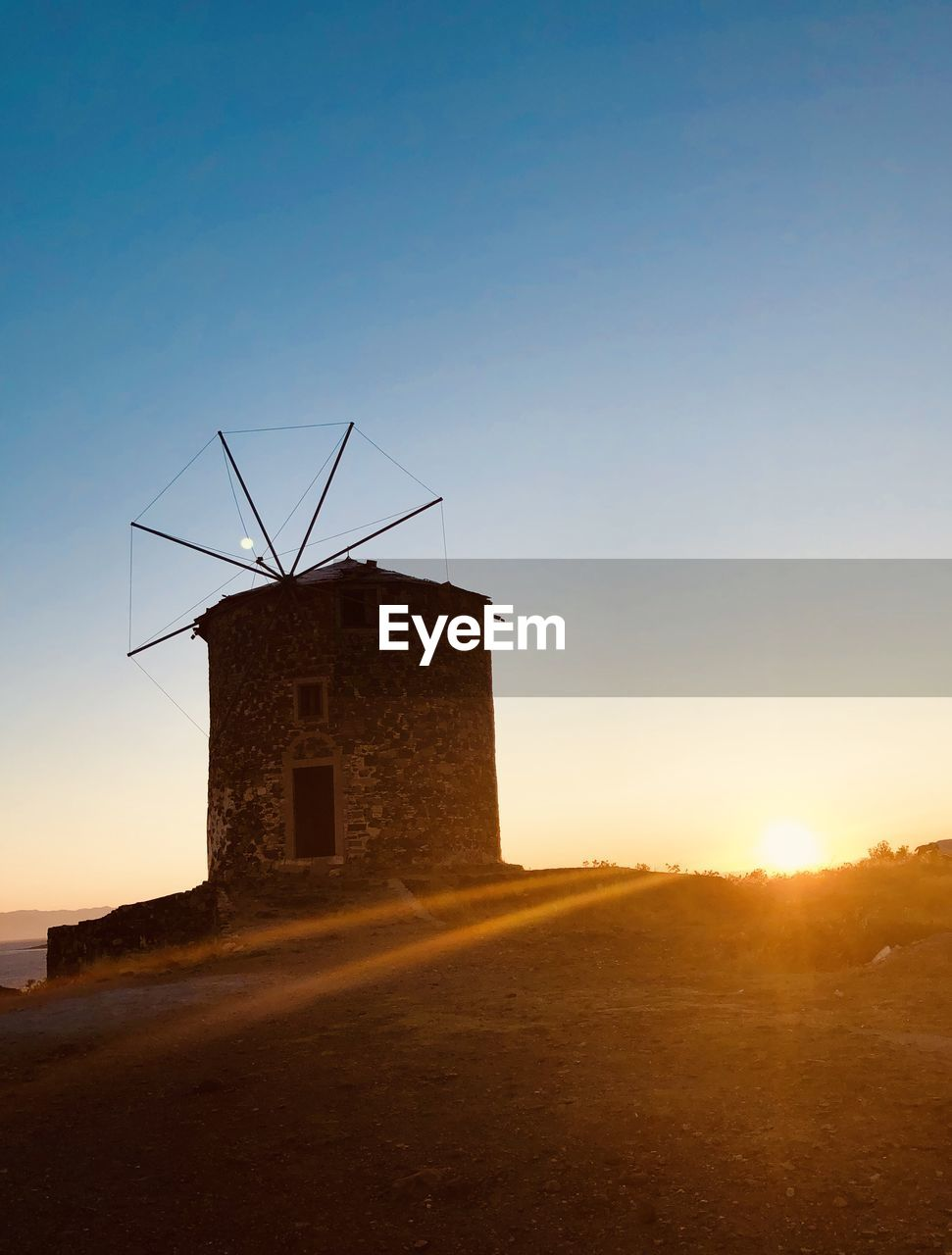 architecture, sky, built structure, building exterior, sunset, environmental conservation, environment, nature, turbine, wind turbine, no people, fuel and power generation, sunlight, wind power, copy space, clear sky, field, land, outdoors, landscape, ruined