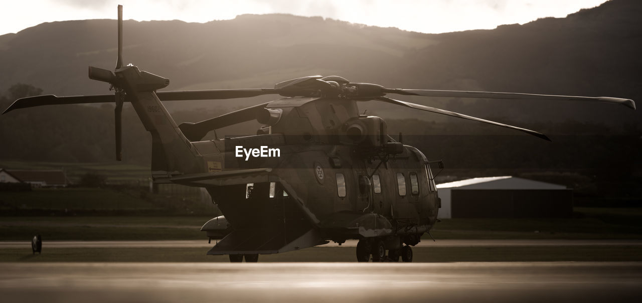 Military Helicopter On Airport Runway Against Mountains