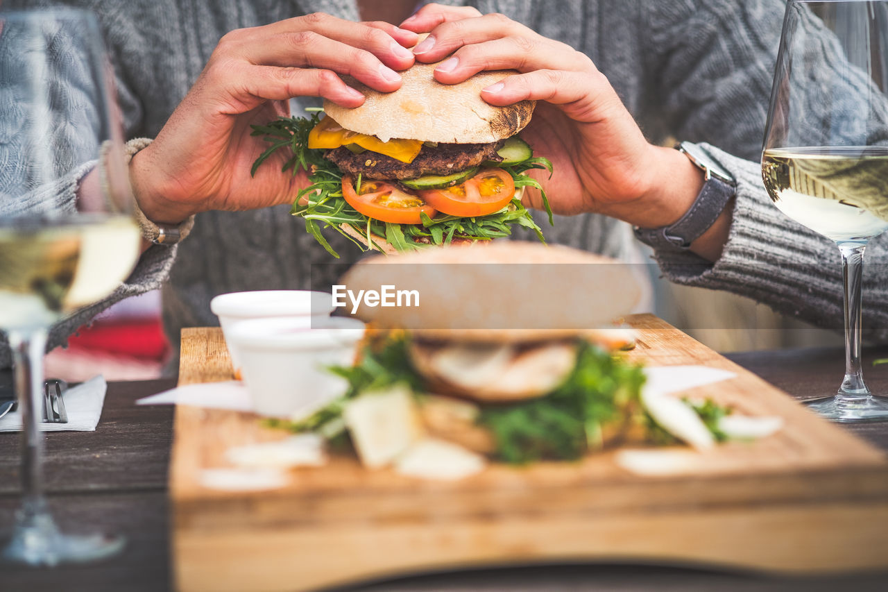 food and drink, food, real people, ready-to-eat, sandwich, human hand, burger, hand, freshness, fast food, one person, selective focus, bread, lifestyles, unhealthy eating, human body part, holding, table, hamburger, take out food, temptation