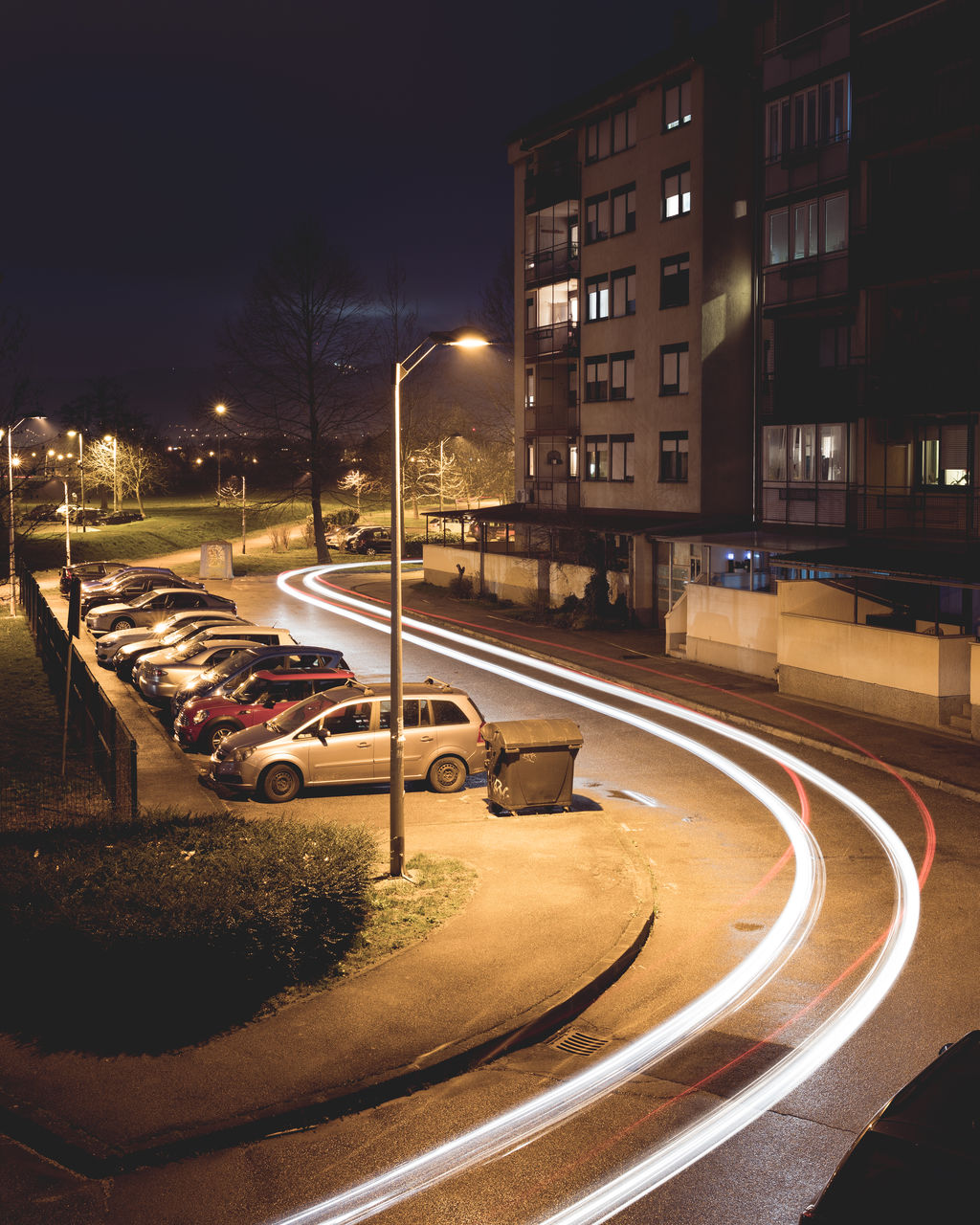 transportation, city, night, architecture, street, road, building exterior, illuminated, mode of transportation, motor vehicle, car, built structure, land vehicle, street light, motion, no people, speed, nature, curve, building, outdoors