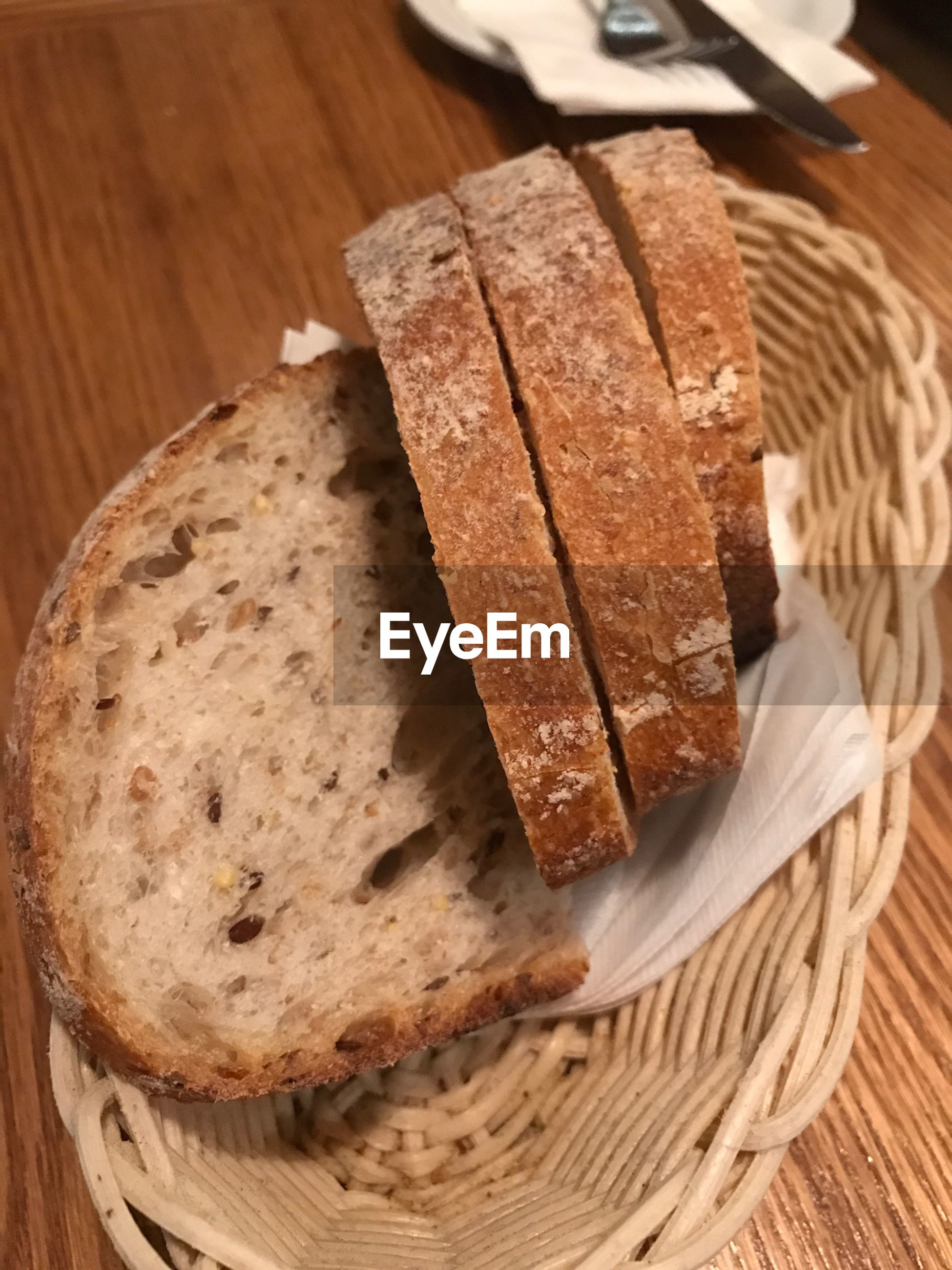 High angle view of fresh slice bread in basket on wooden table