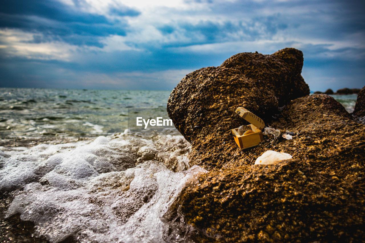 Rocks on shore at beach against sky