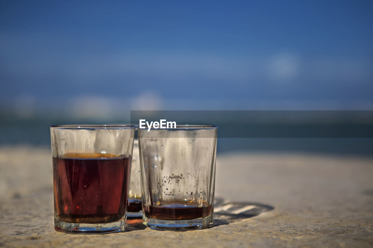 refreshment, drink, glass, drinking glass, household equipment, alcohol, food and drink, focus on foreground, no people, beach, water, glass - material, table, transparent, close-up, day, sky, sea, land