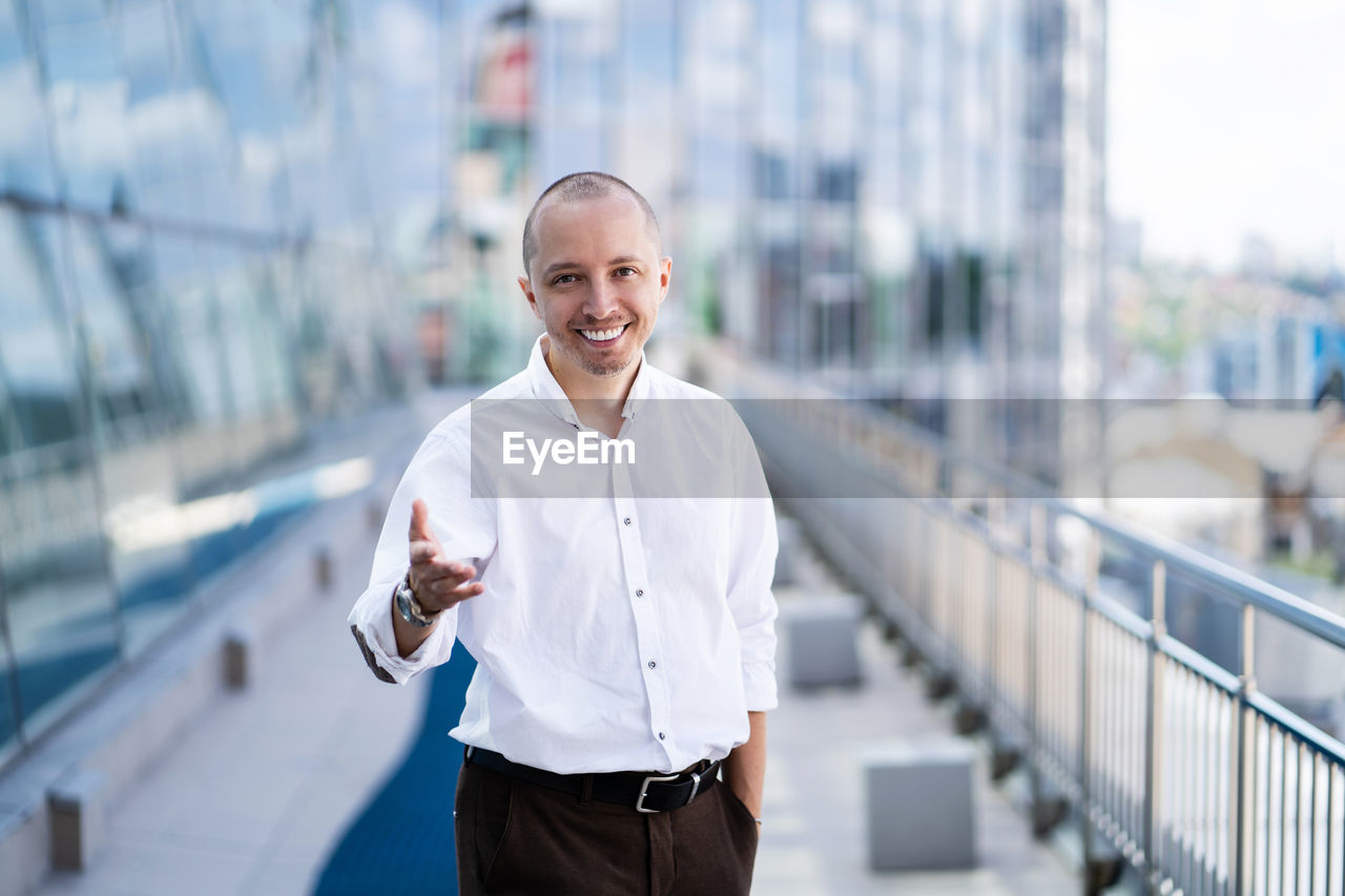 PORTRAIT OF SMILING MAN STANDING AGAINST RAILING