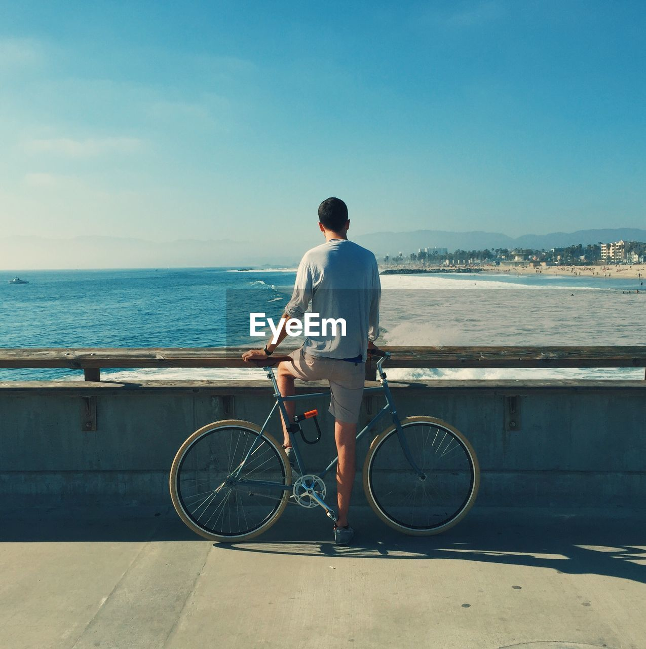 Rear View Of Man With Bicycle By Sea Against Clear Sky