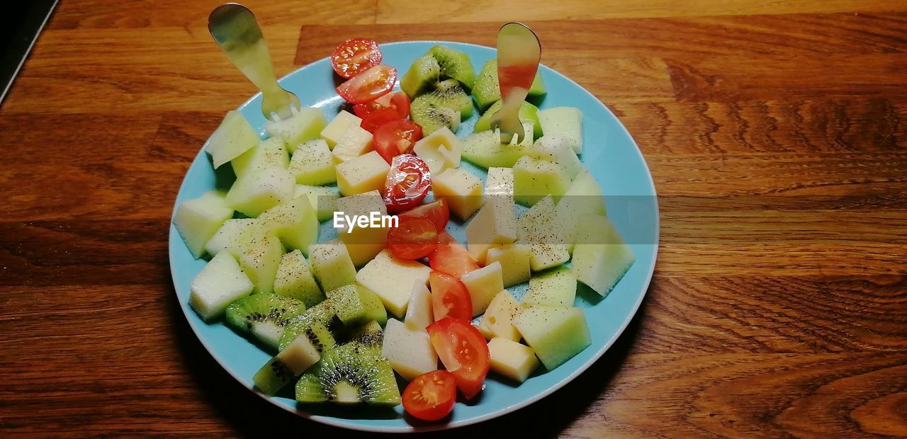 food and drink, table, food, healthy eating, ready-to-eat, wellbeing, freshness, fruit, vegetable, salad, indoors, still life, bowl, serving size, plate, high angle view, no people, wood - material, close-up, slice, fruit salad, chopped