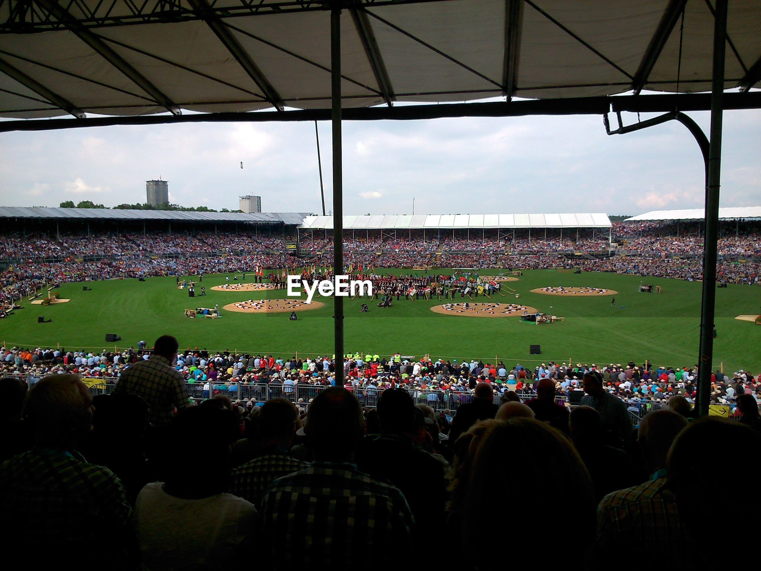 large group of people, crowd, men, person, lifestyles, leisure activity, stadium, sky, mixed age range, relaxation, sitting, spectator, arts culture and entertainment, built structure, grass, enjoyment, togetherness, outdoors