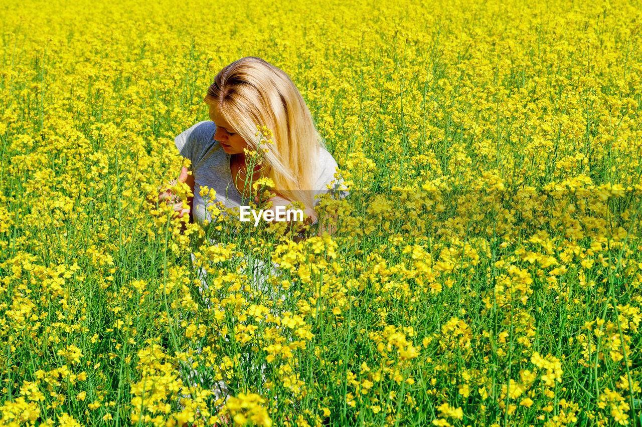 Woman amidst flowers on oilseed rape field