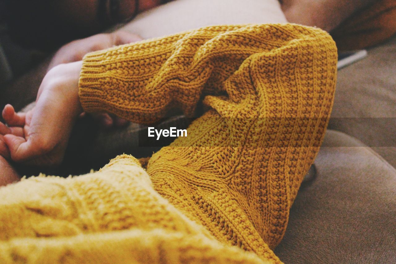 Close-Up Of Person Wearing Sweater Lying On Sofa
