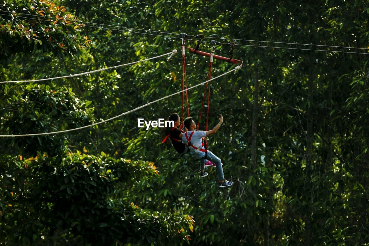 tree, hanging, rope, adventure, full length, day, leisure activity, fun, outdoors, togetherness, mid-air, gripping, two people, challenge, growth, swing, courage, childhood, girls, rope swing, real people, nature, boys, young adult, people