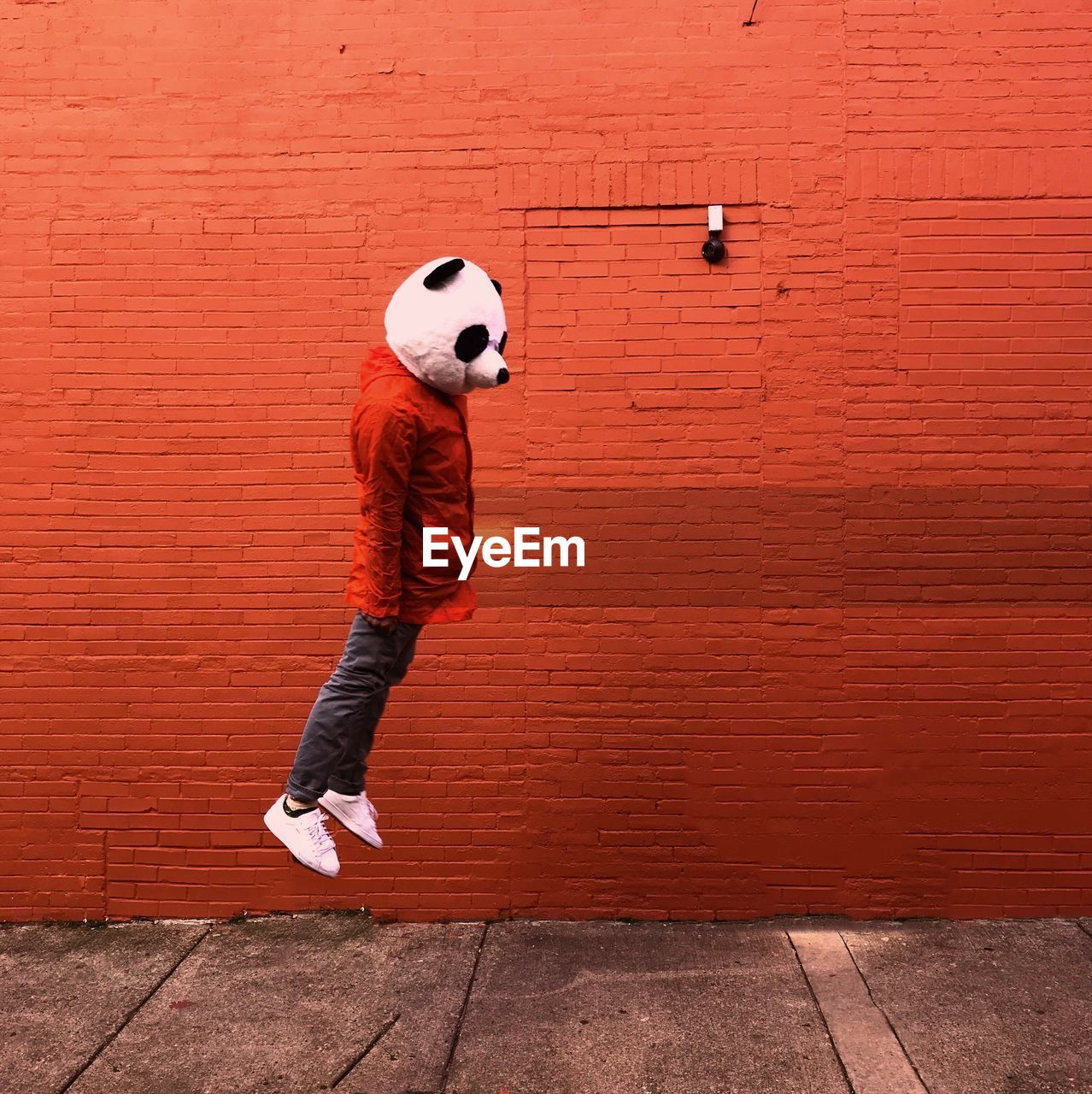 Side of person jumping against wall