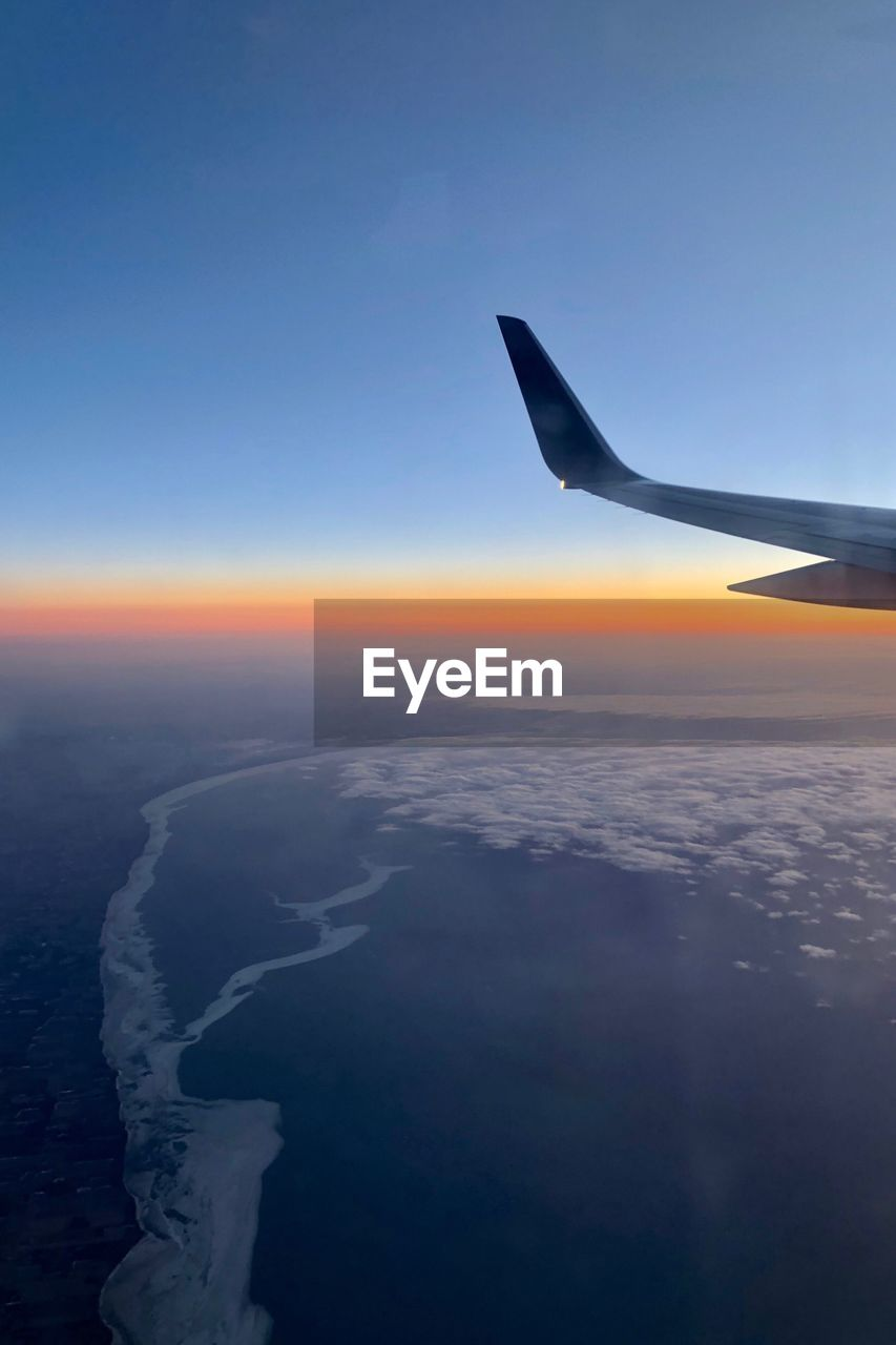 sky, airplane, air vehicle, beauty in nature, flying, cloud - sky, scenics - nature, transportation, sunset, aircraft wing, nature, travel, aerial view, mode of transportation, blue, no people, mid-air, tranquil scene, tranquility, environment, outdoors