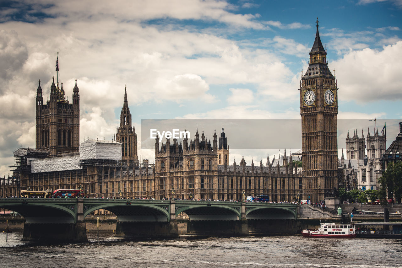water, architecture, river, cloud - sky, tower, clock tower, travel destinations, built structure, sky, waterfront, bridge - man made structure, building exterior, connection, day, transportation, nautical vessel, outdoors, city, riverbank, no people
