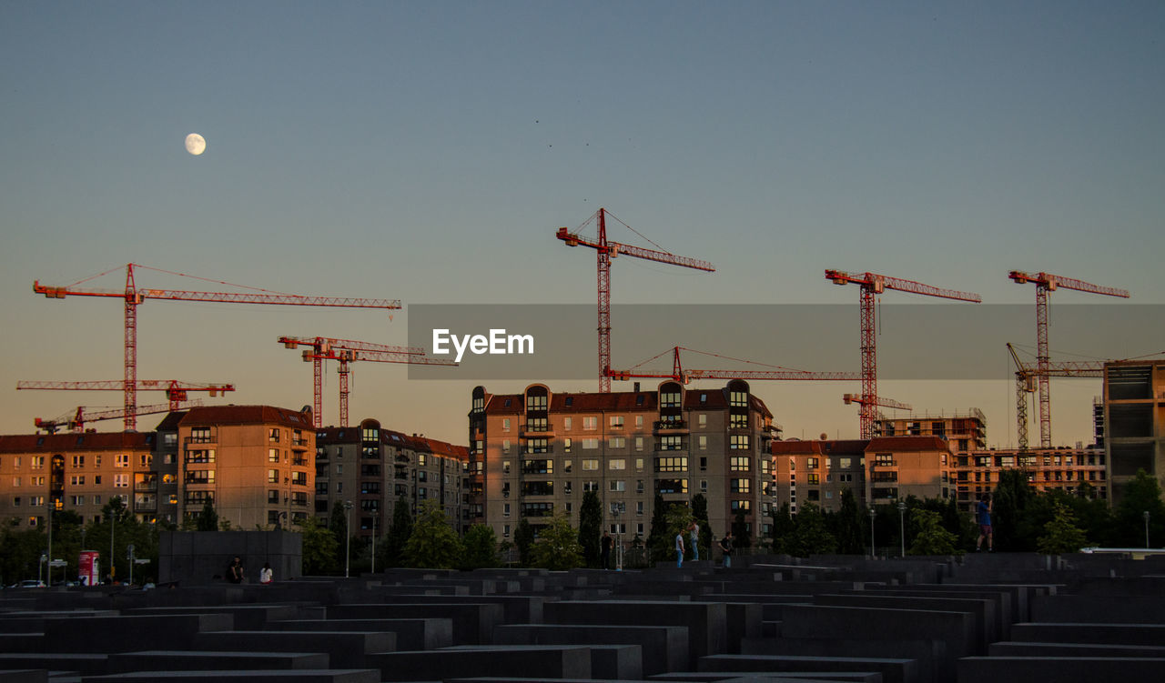Cranes In City Against Clear Sky During Sunset