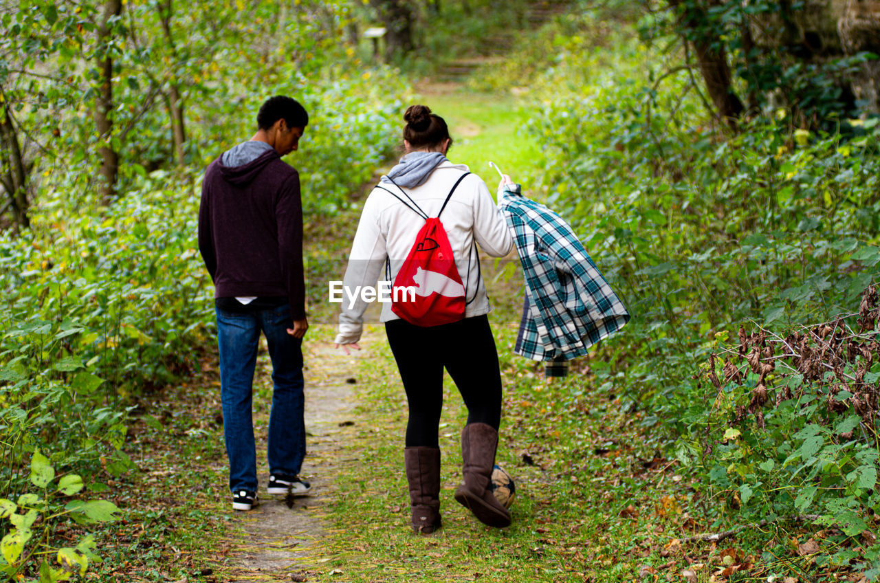 rear view, full length, two people, togetherness, plant, land, men, casual clothing, young adult, day, walking, leisure activity, tree, lifestyles, nature, people, forest, young men, real people, adult, outdoors, couple - relationship