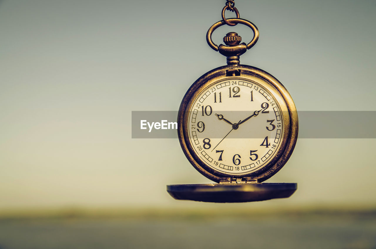 Close-up of clock against sky