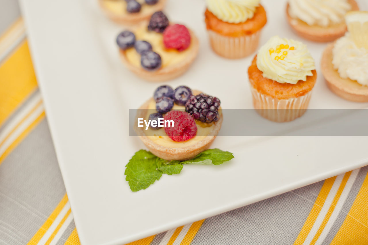High Angle View Of Tarts And Cupcakes In Plate On Table