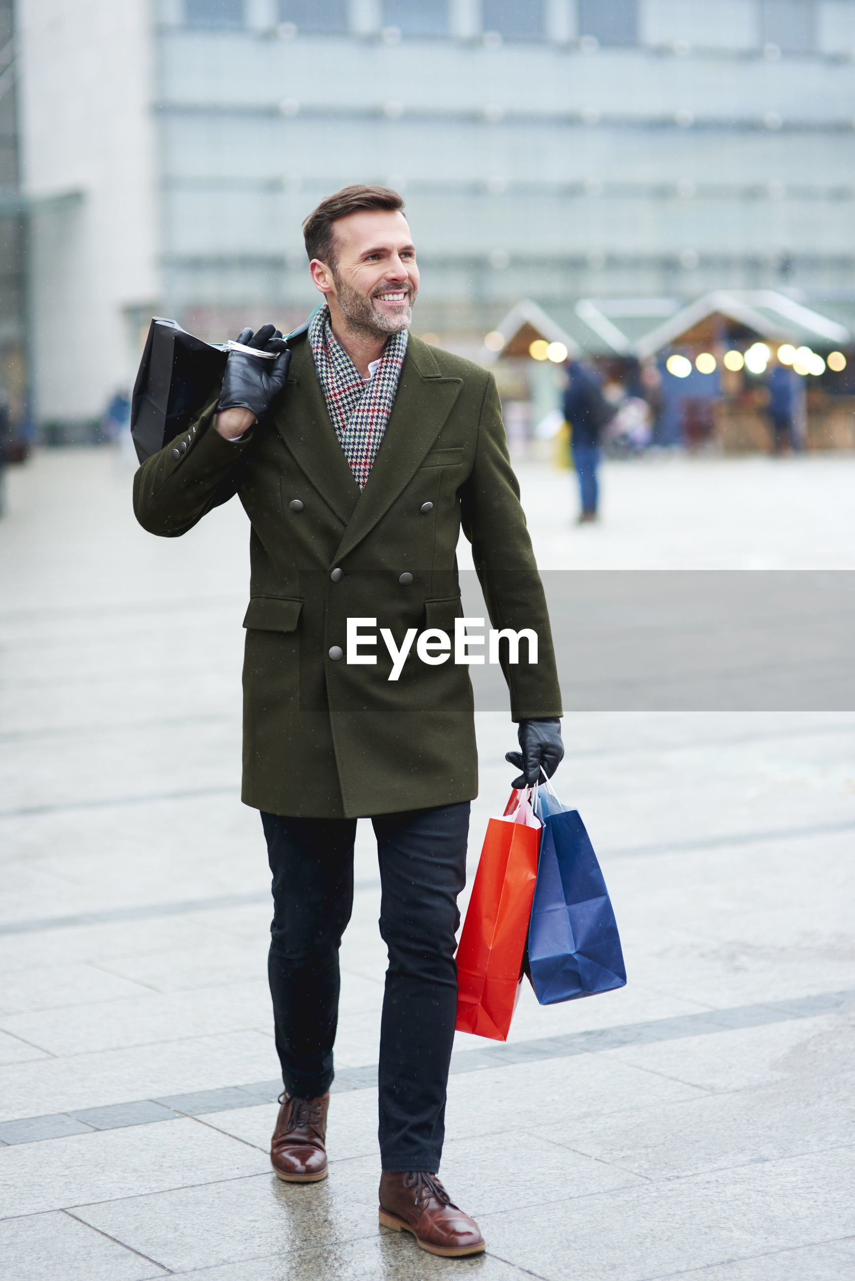 Man holding shopping bags while walking in city during winter