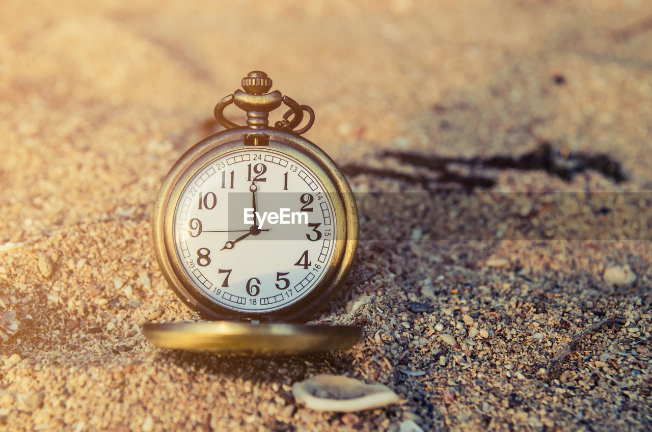 Close-up of clock on sand