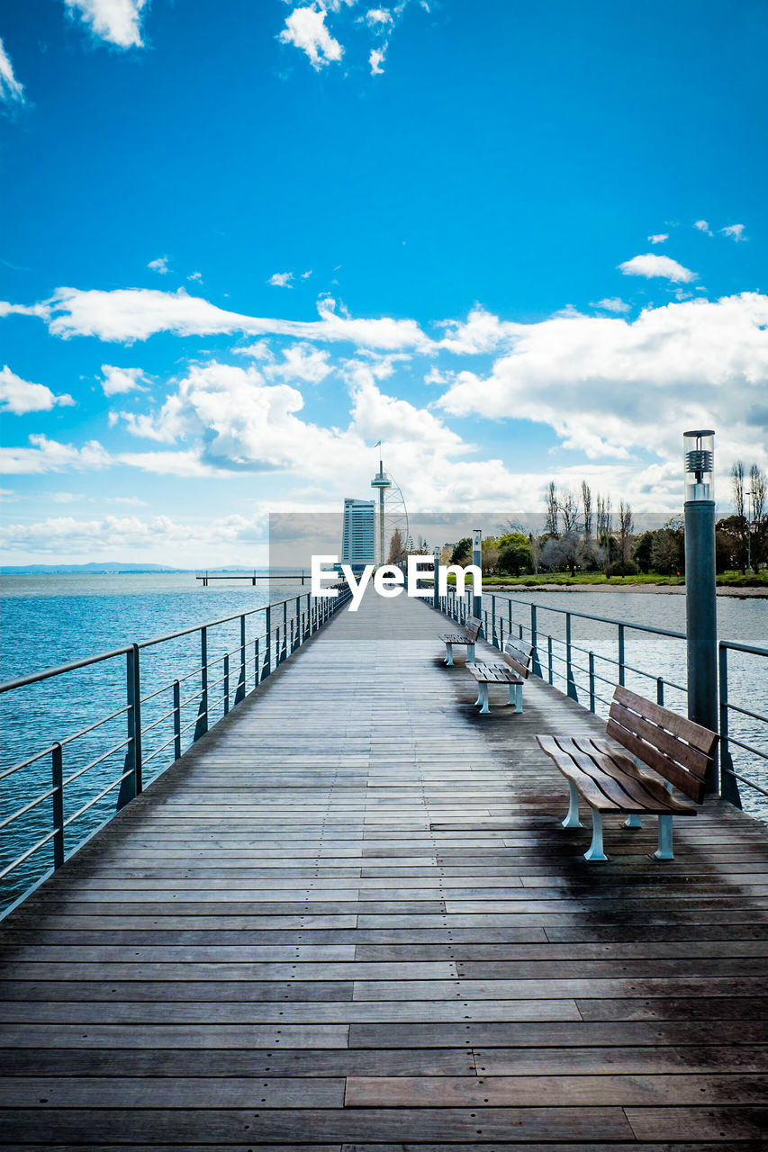 sky, cloud - sky, water, the way forward, architecture, sea, railing, direction, built structure, wood - material, nature, pier, no people, day, diminishing perspective, tranquility, empty, blue, tranquil scene, wood, outdoors, horizon over water, wood paneling, long