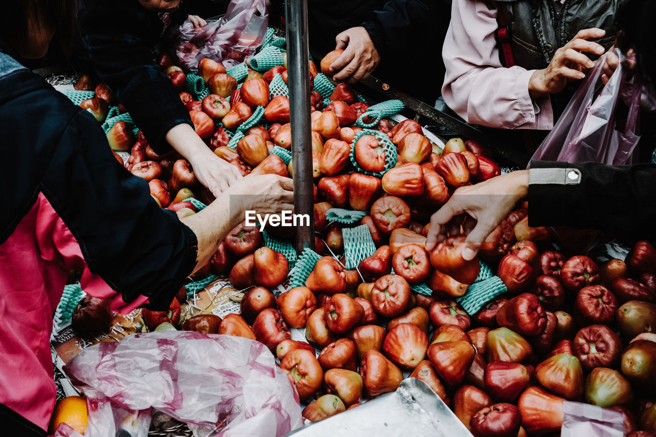 Midsection people purchasing fruits in market