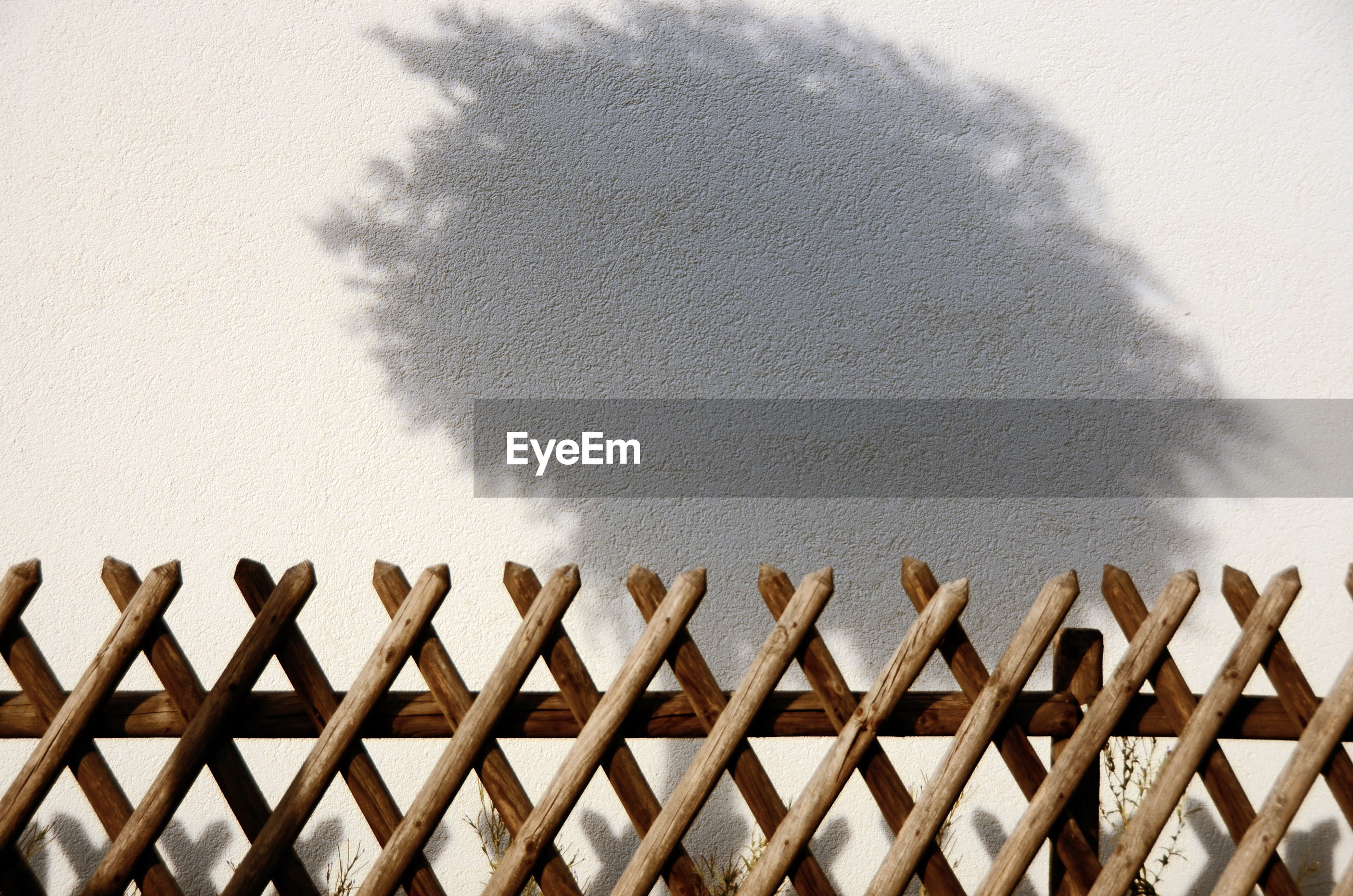 HIGH ANGLE VIEW OF WALL WITH SHADOW ON FENCE