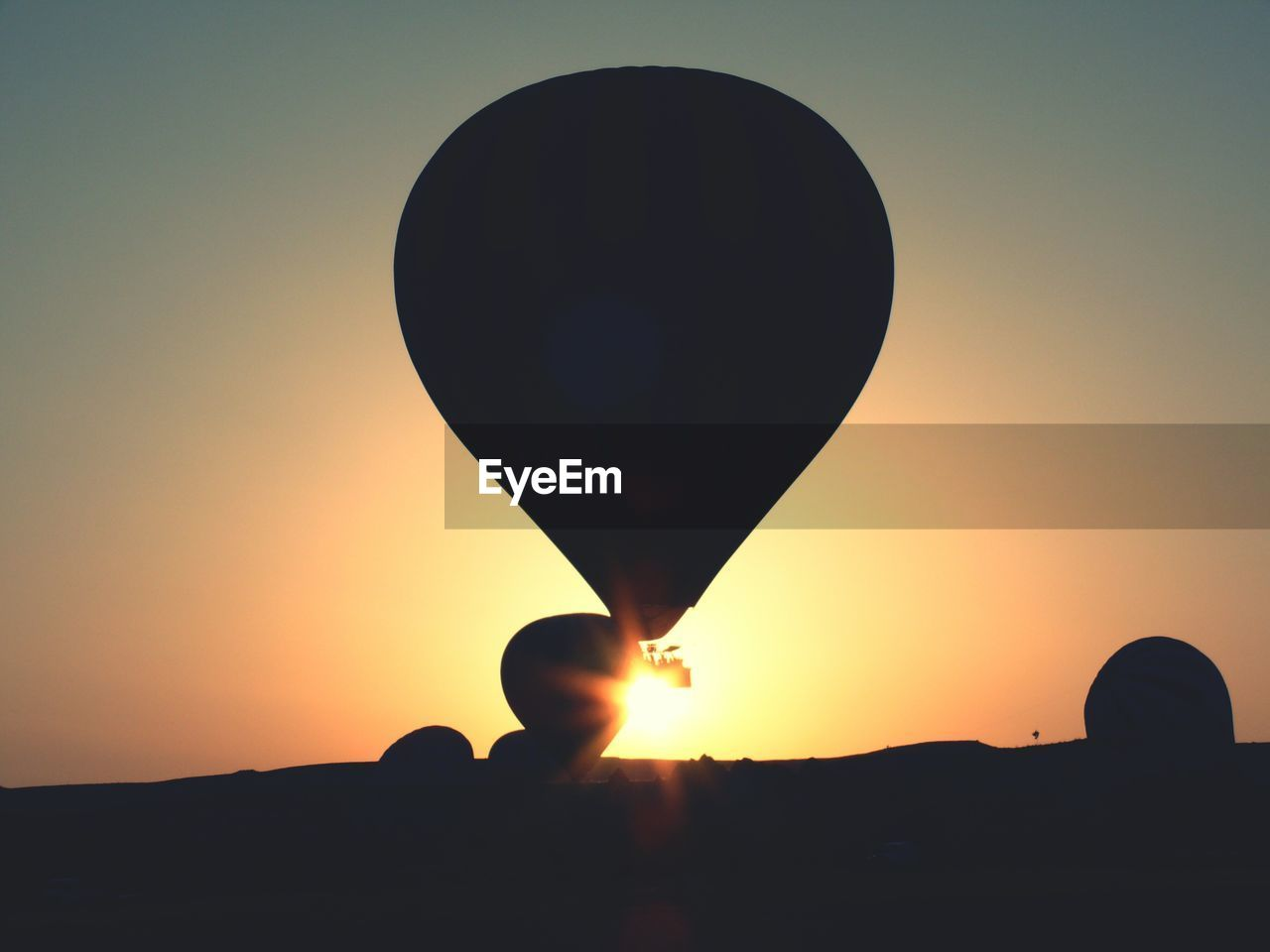 sunset, sky, orange color, sun, air vehicle, balloon, silhouette, hot air balloon, beauty in nature, nature, scenics - nature, flying, transportation, sunlight, mid-air, clear sky, outdoors, no people, adventure, lens flare, ballooning festival