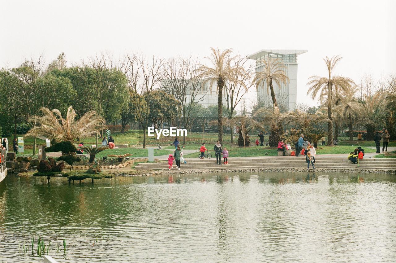 People Enjoying By Lake At Park