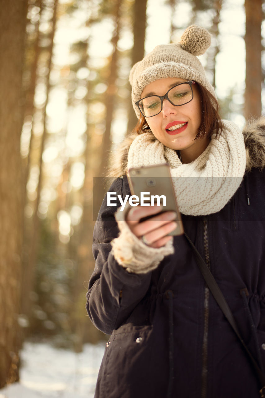 wireless technology, winter, smart phone, mobile phone, portable information device, young adult, technology, warm clothing, clothing, young women, communication, connection, one person, real people, cold temperature, smiling, using phone, telephone, lifestyles, tree, scarf, outdoors, beautiful woman