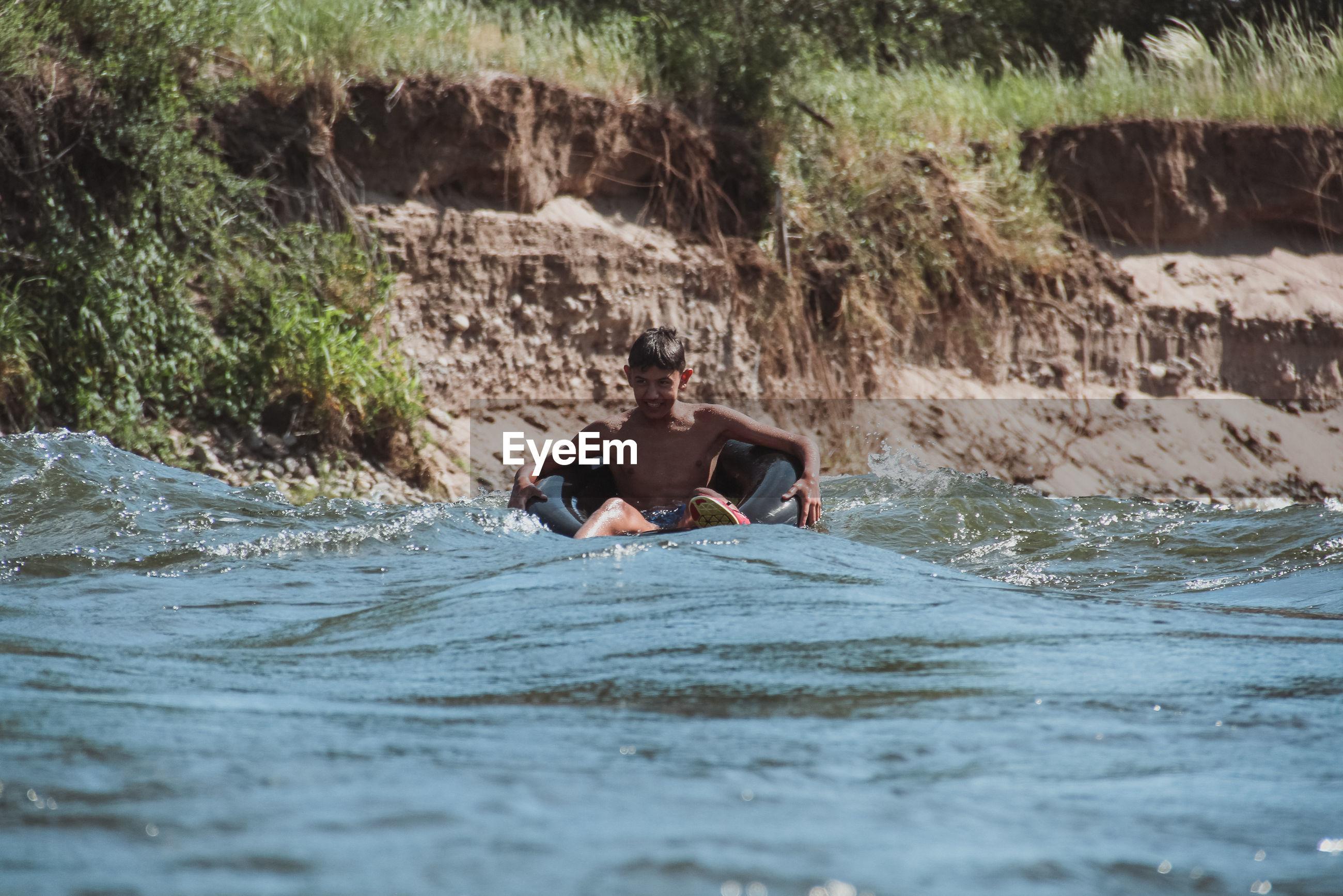 Boy sitting on boat in river