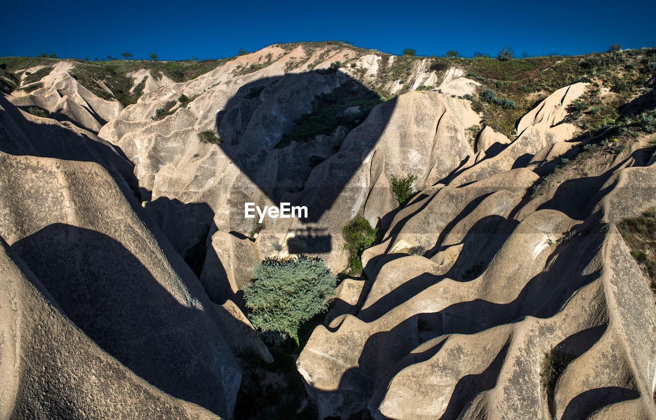 Shadow Of Hot Air Balloon On Rock Formations At Cappadocia