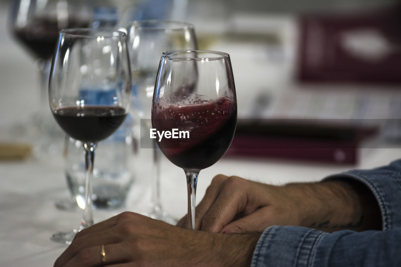 alcohol, wineglass, human hand, wine, hand, drink, glass, refreshment, food and drink, human body part, real people, holding, one person, lifestyles, red wine, focus on foreground, men, indoors, adult, finger