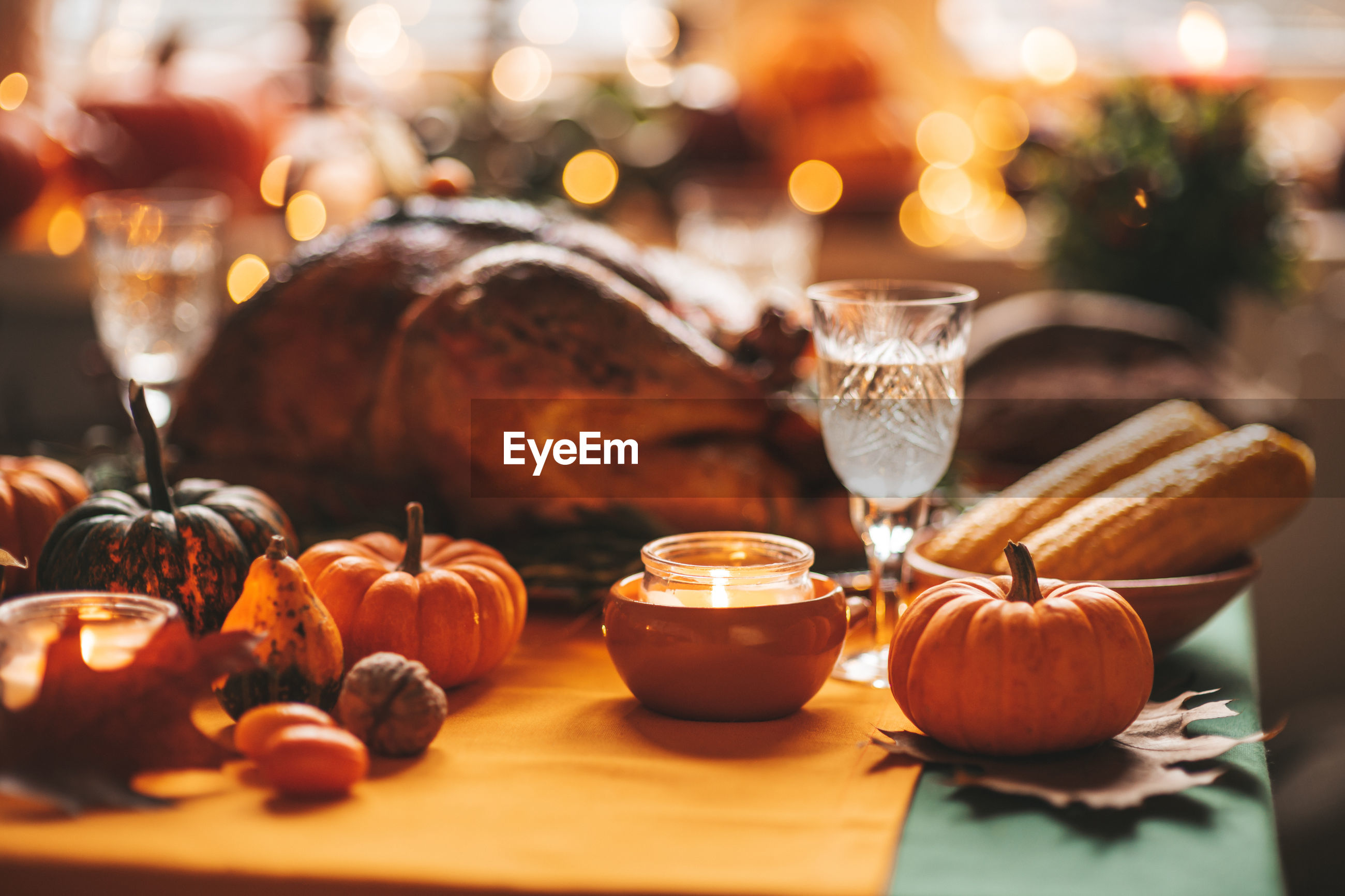 CLOSE-UP OF PUMPKIN WITH GLASSES ON TABLE