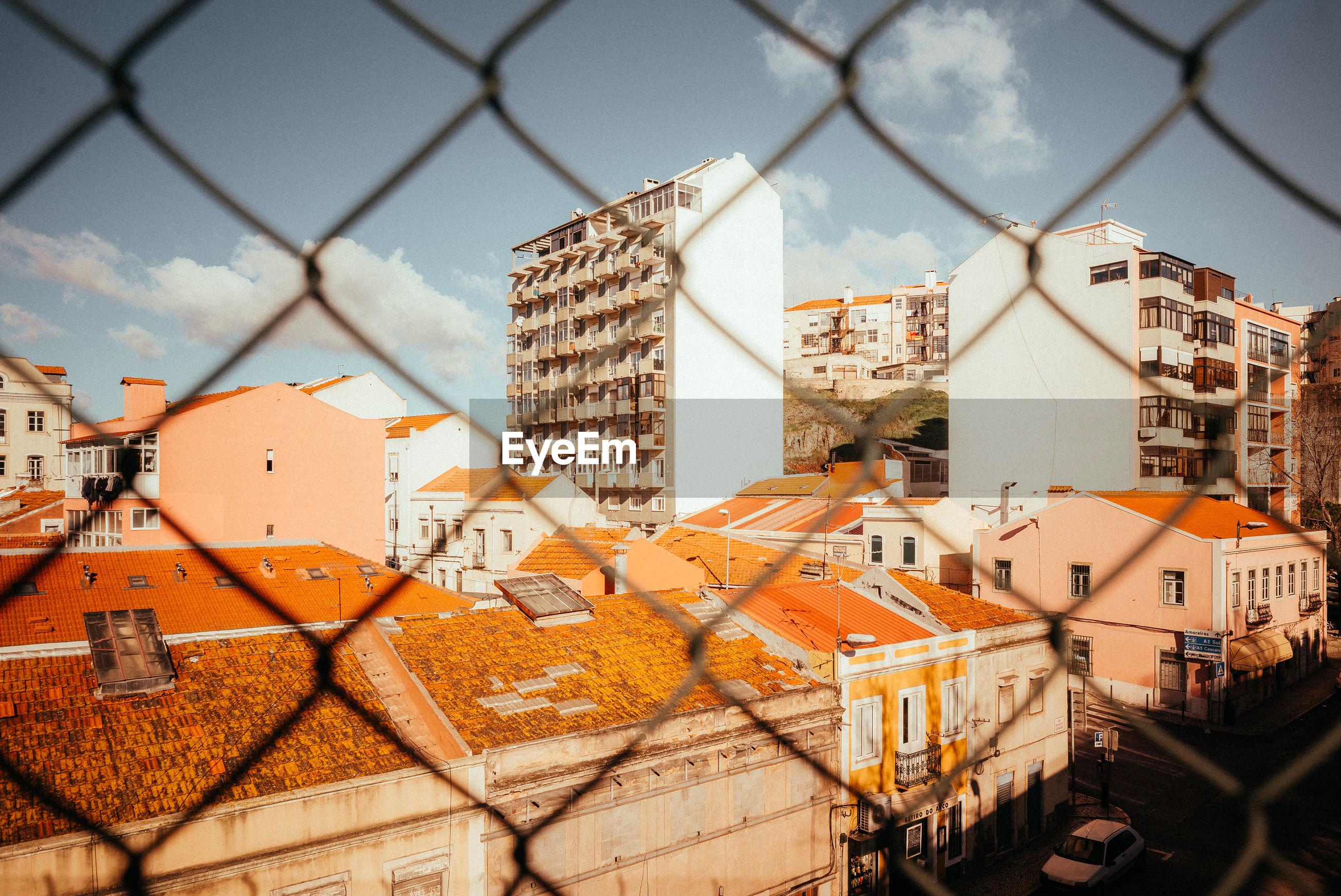 Buildings against sky seen through chainlink fence
