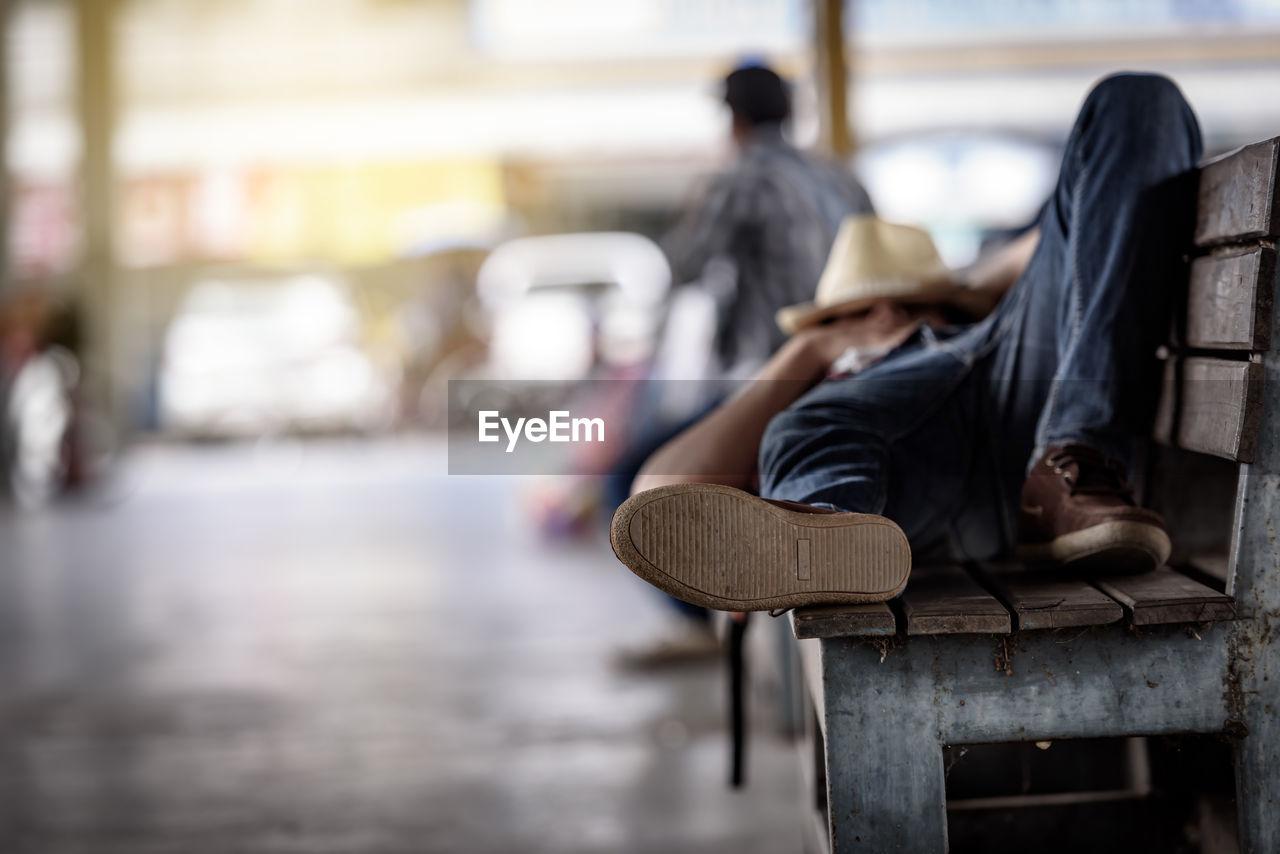 Full length of man sleeping on bench