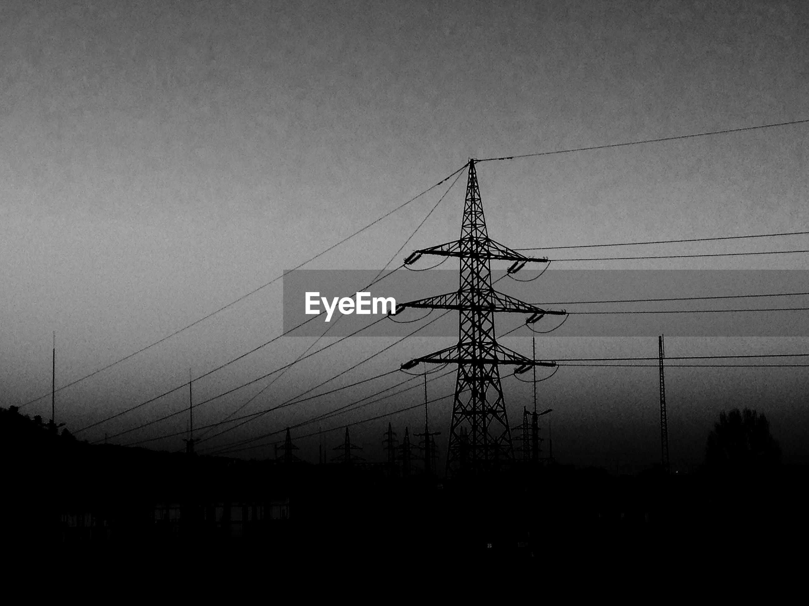 Low angle view of silhouette electricity pylon against sky at night