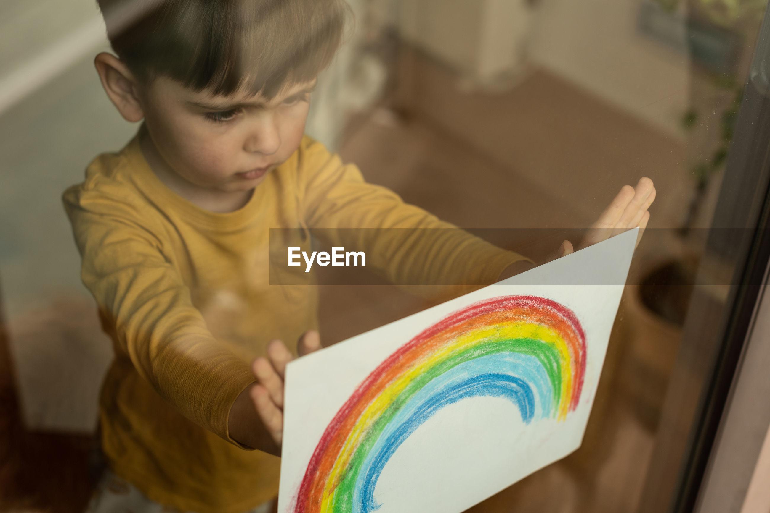 Boy holding rainbow drawing seen through window