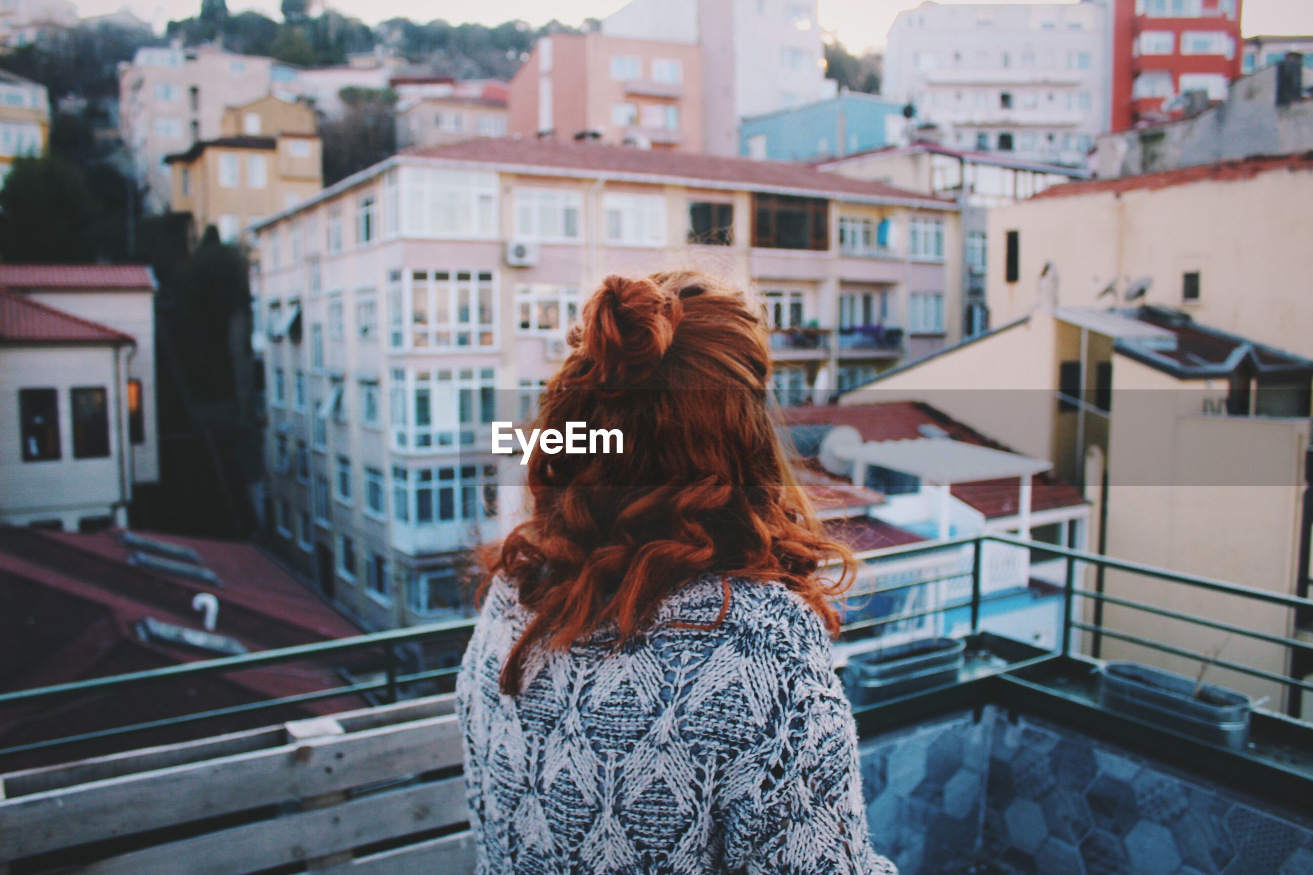 Rear view of woman looking at city from balcony