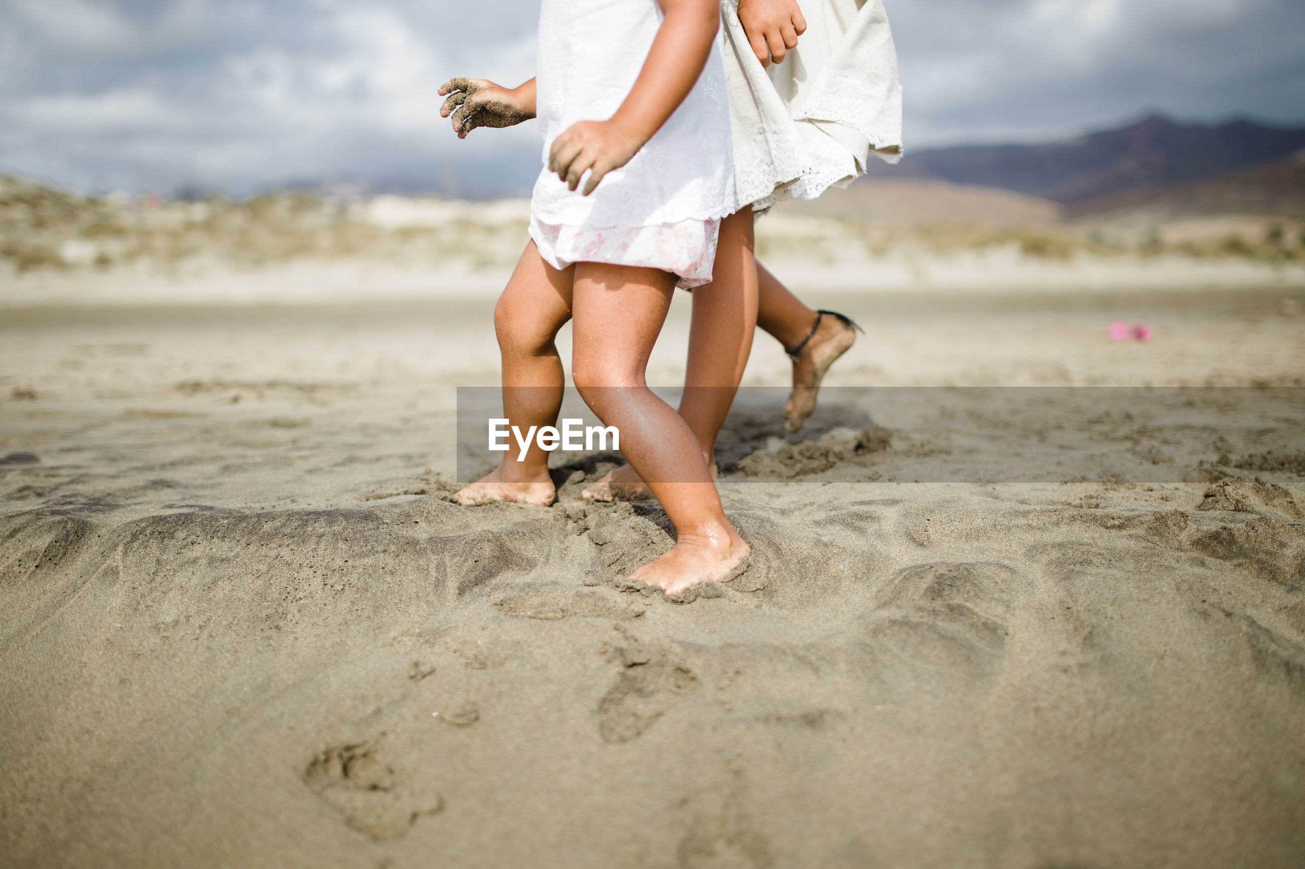 Low section of girls walking on sandy beach
