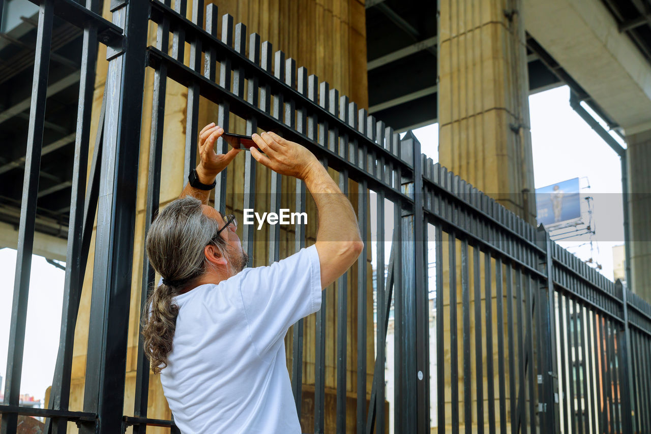 Mature Man Photographing While Standing By Fence