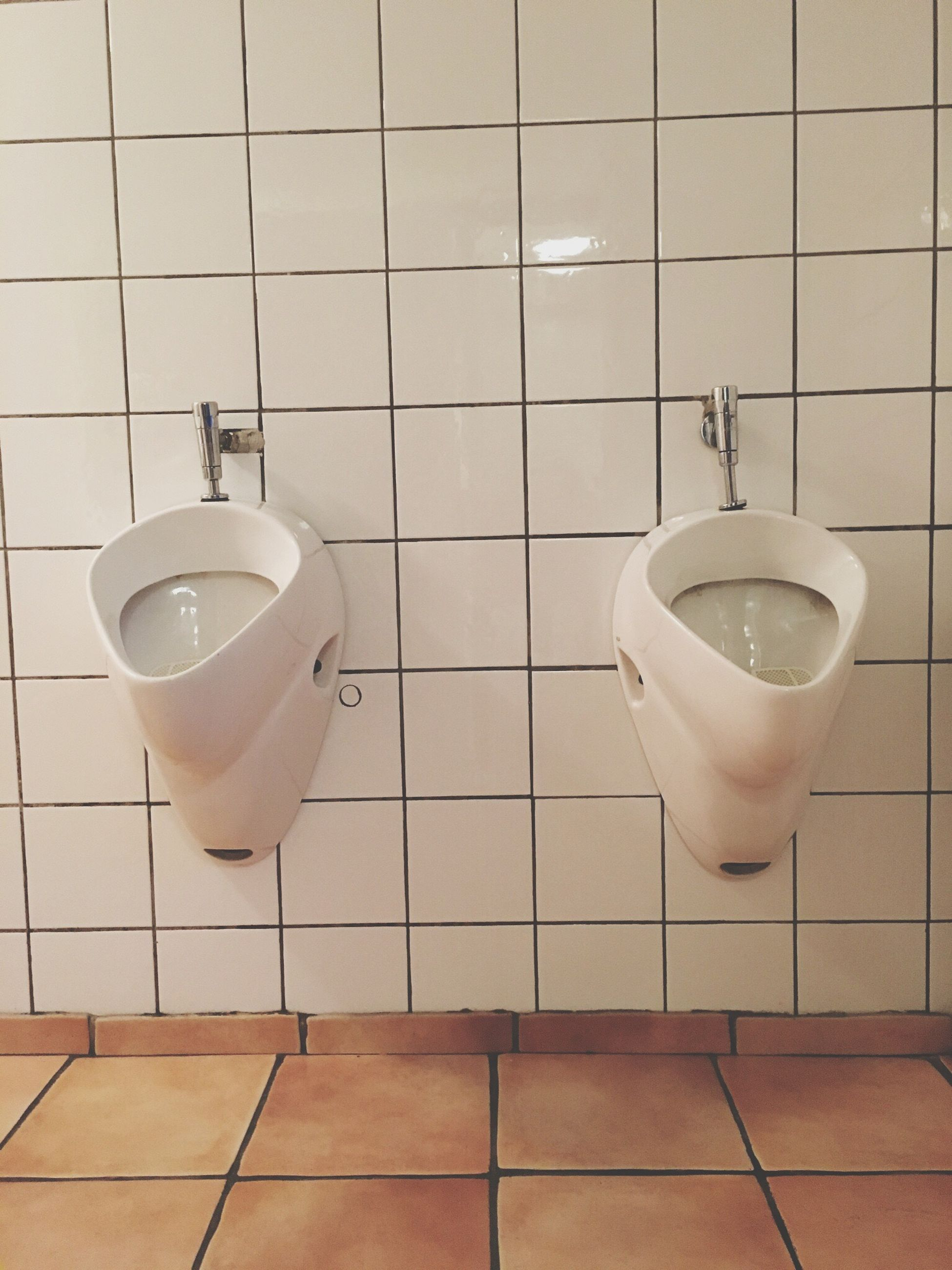 Urinals on white tile wall at public restroom