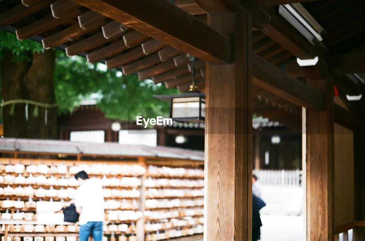 Rear view of man standing by prayer blocks at meiji-jingu shrine