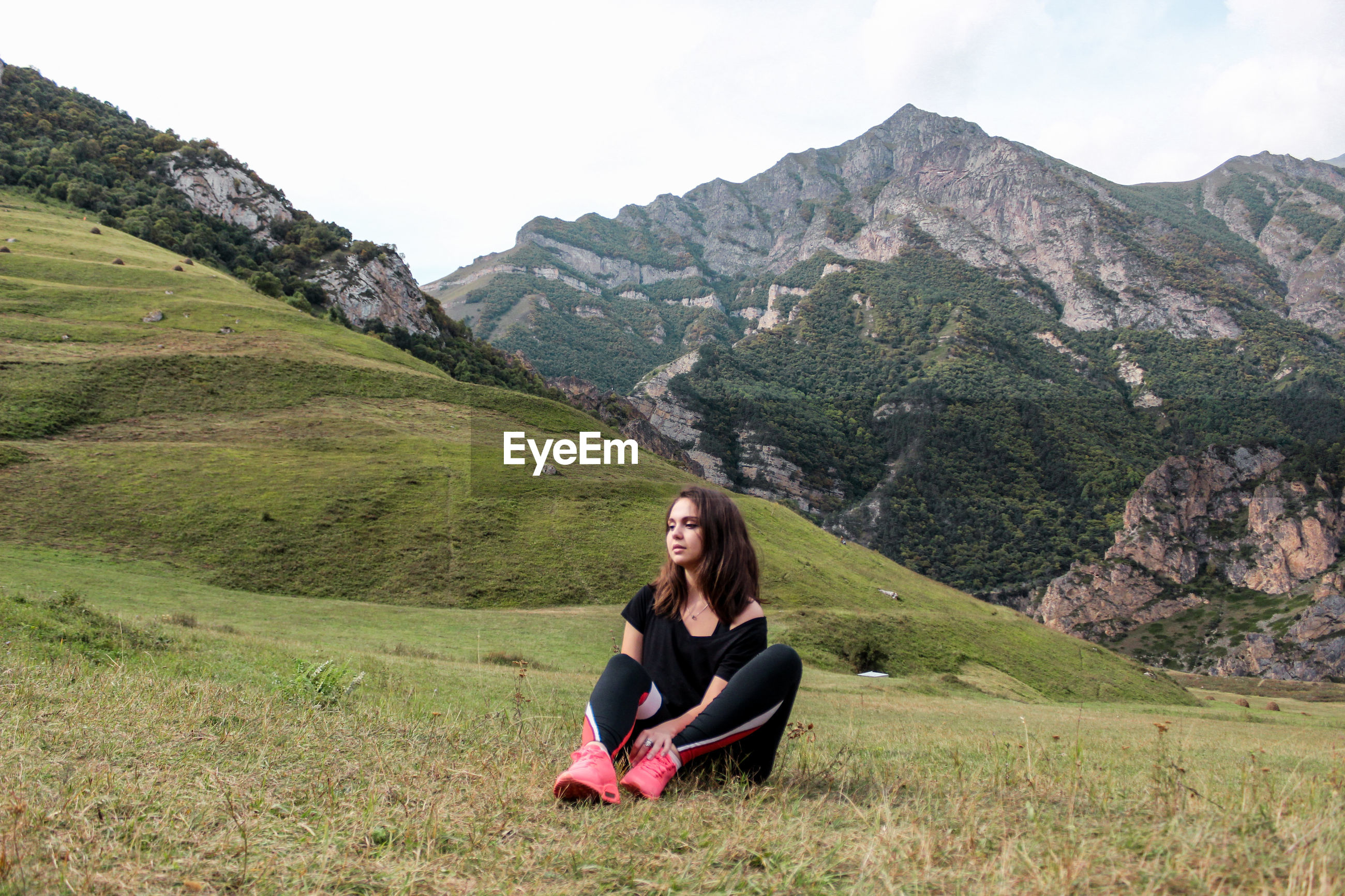 Young woman sitting on field against mountains