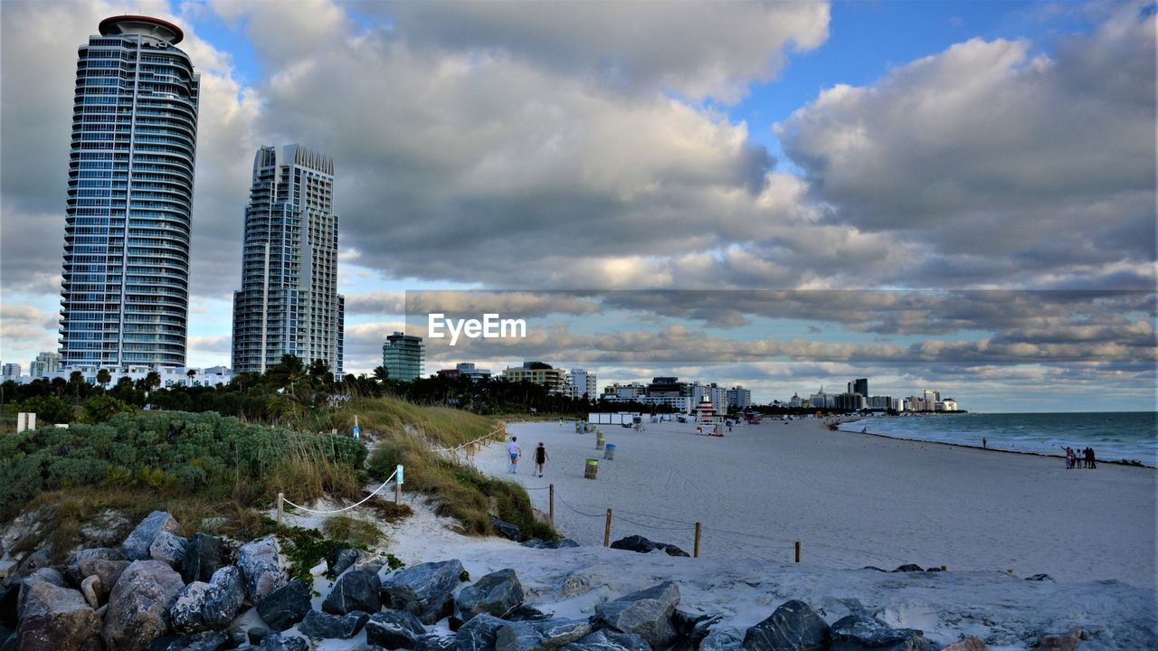 cloud - sky, sky, architecture, built structure, building exterior, water, nature, city, sea, beach, building, land, scenics - nature, office building exterior, outdoors, beauty in nature, incidental people, day, skyscraper, modern
