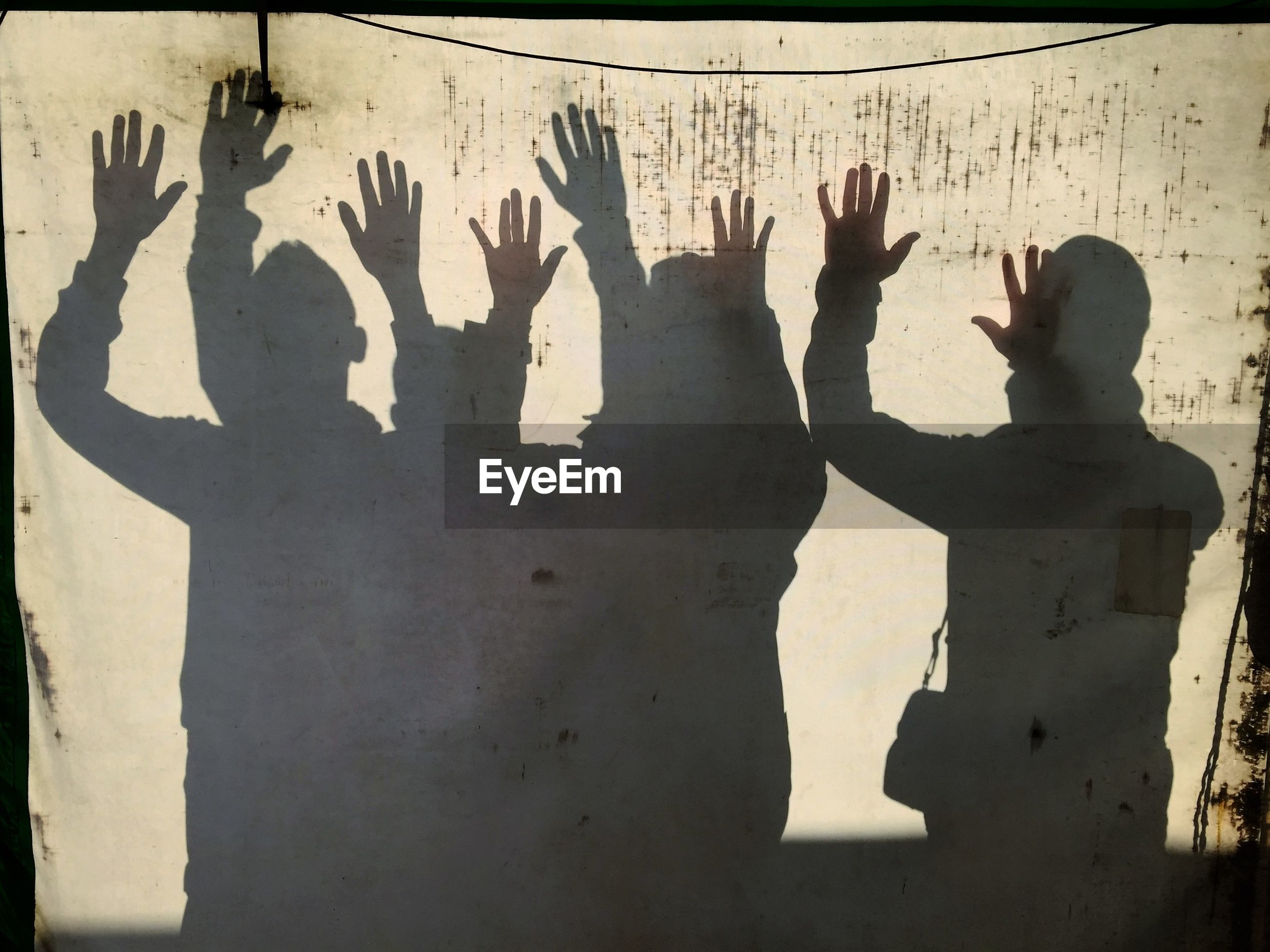 Shadow of people with arms raised on wall